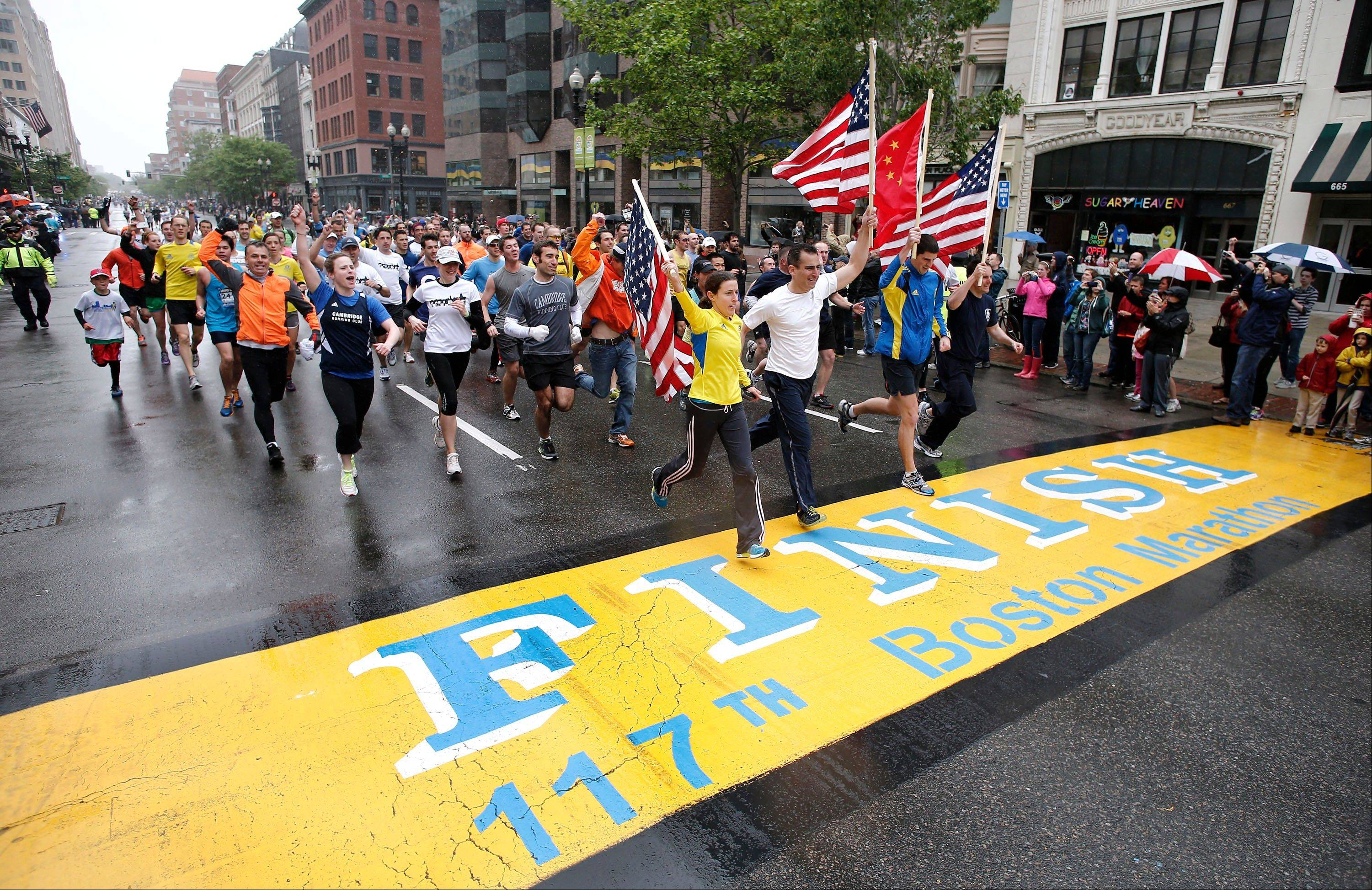 Runners who were unable to finish the Boston Marathon on April 15 because of the bombings cross the finish line on Boylston Street after the city allowed them to finish the last mile of the race in Boston, Saturday, May 25.