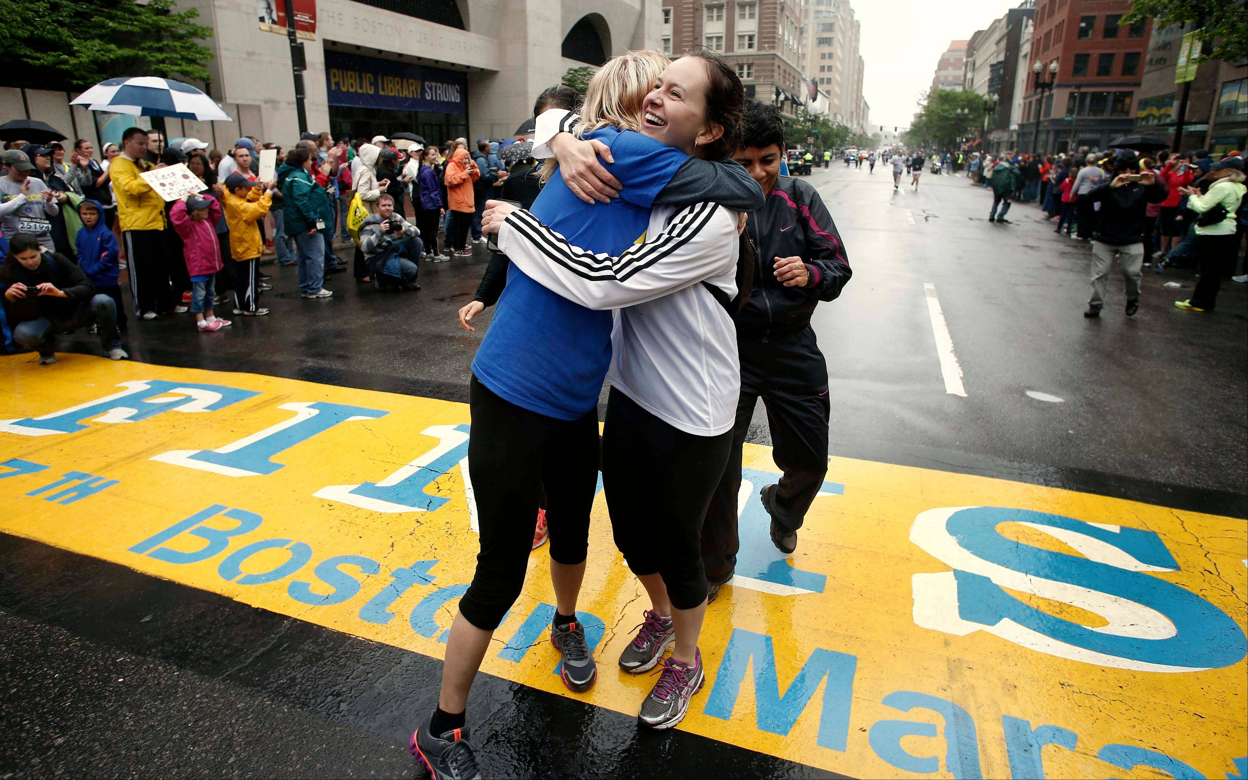 Rachel, left, and Pam Vingsness of Newton, Mass., hug each other after crossing the finish line as runners who were unable to finish the Boston Marathon on April 15 because of the bombings were allowed to finish the last mile of the race in Boston, Saturday, May 25.