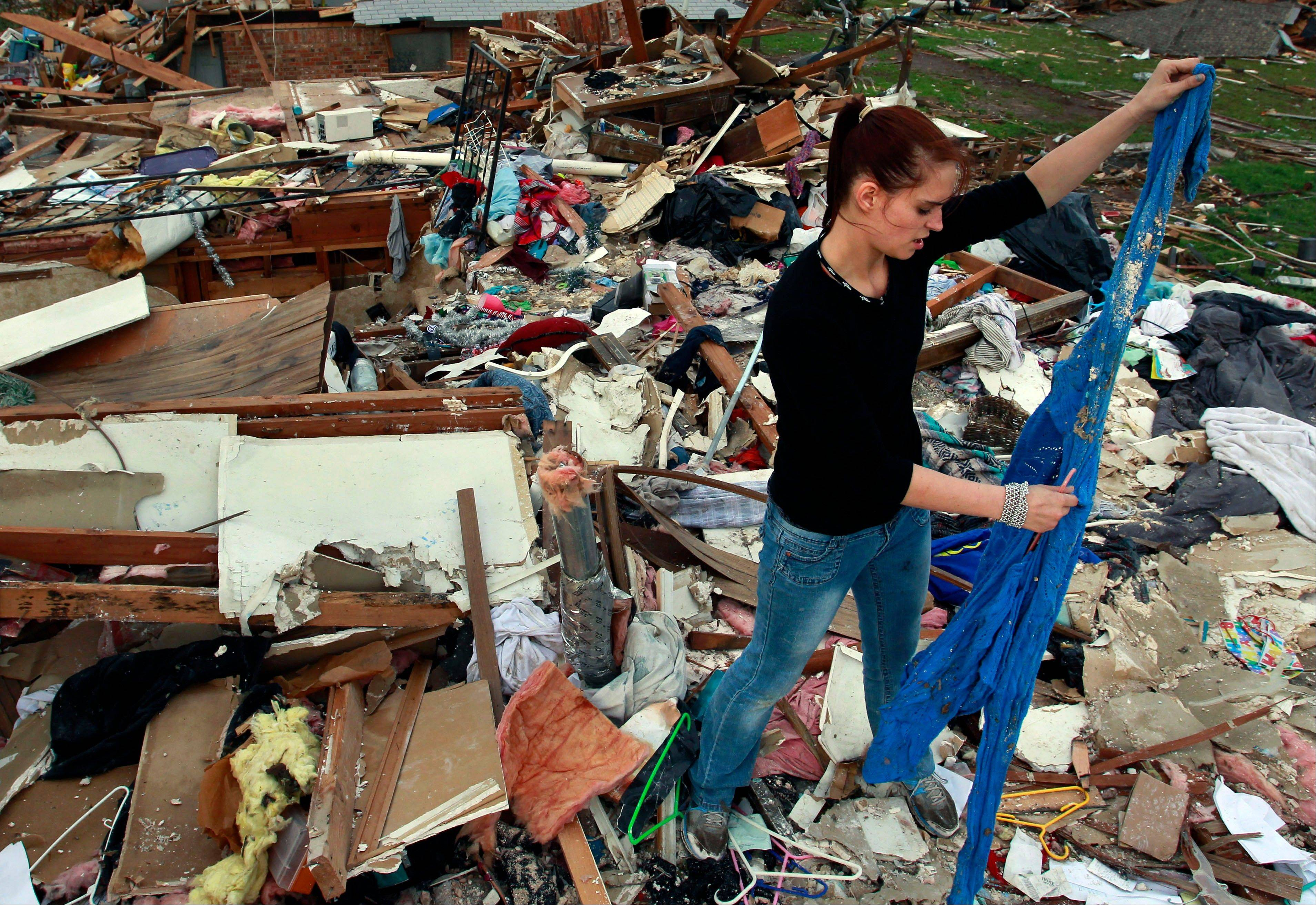 Sabrina Mitchell, 19, examines a sweatshirt on Friday as she salvages items from the wreckage of her home which was destroyed earlier in the week when a tornado hit Moore, Okla.