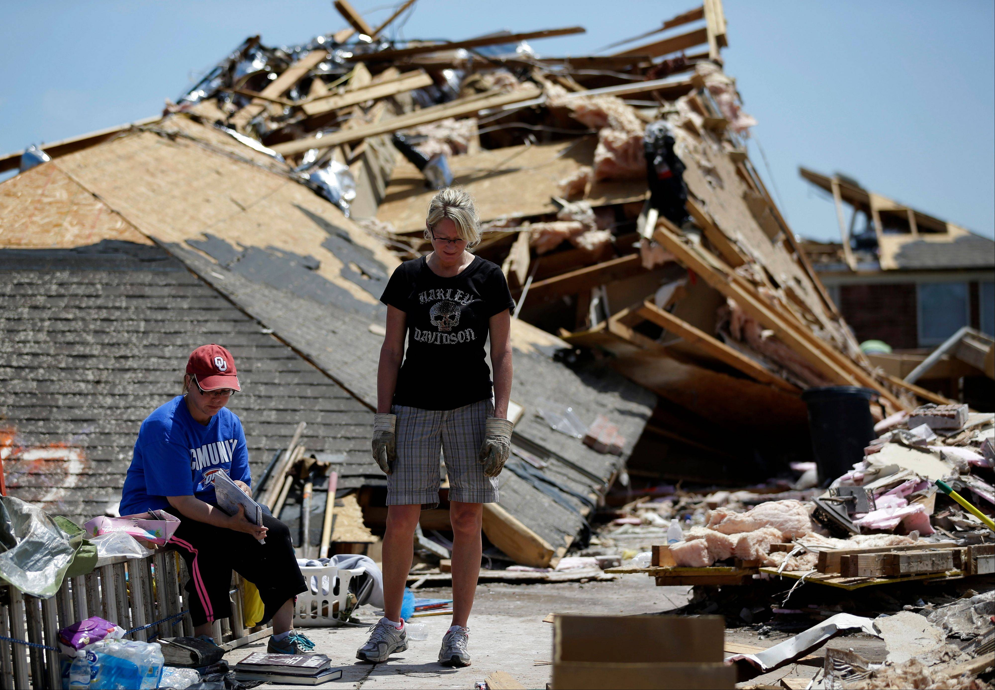 Jennifer Walker, left, sifts through a memories book Wednesday as she and her friend Kate Burger, center, stand in front of what remains of Walker's home. When she moved into her single-story brick house in Moore eight years ago, she considered installing a safe room or bunker to shield her family. She decided against it.