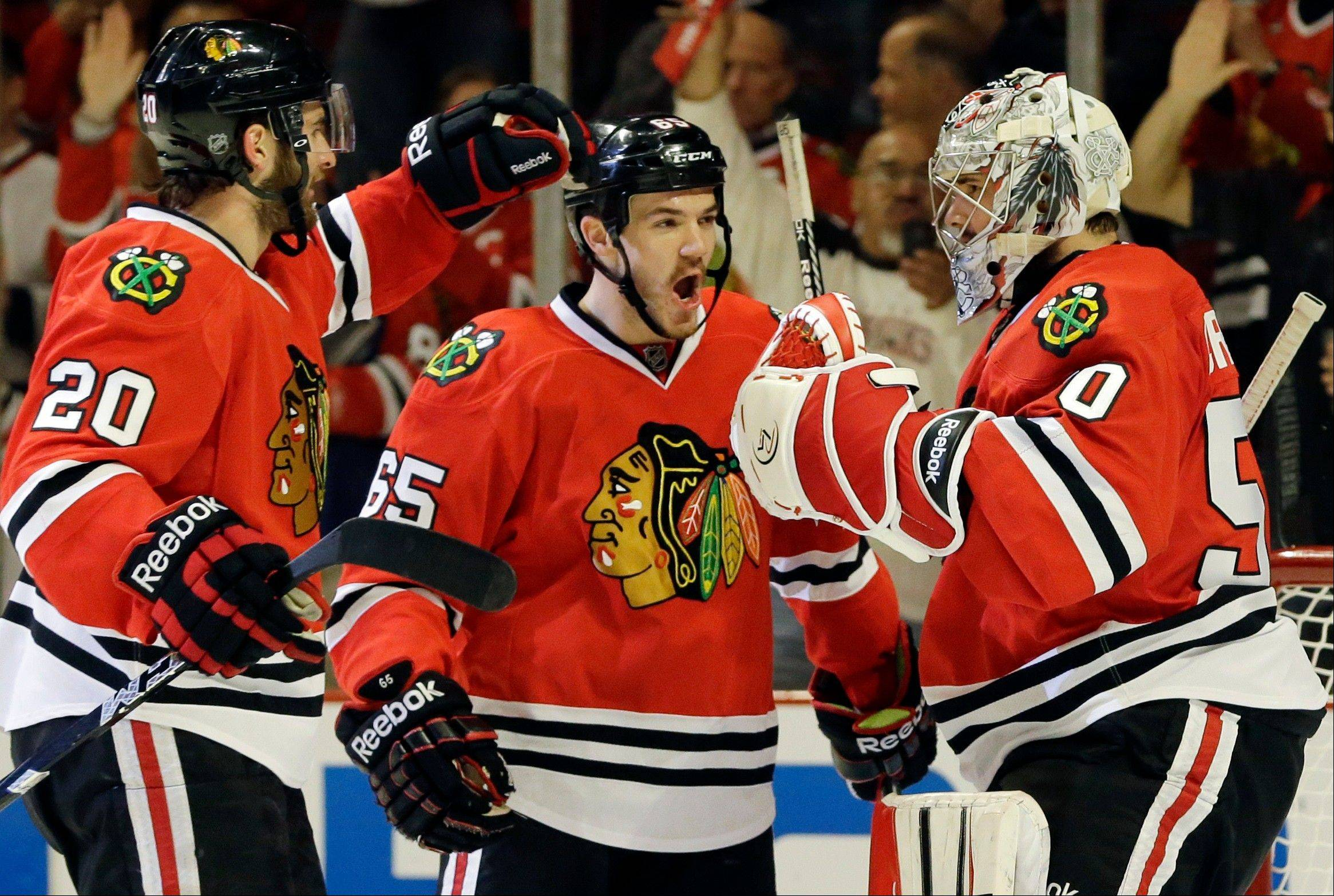 Chicago Blackhawks goalie Corey Crawford, right, celebrates with teammates Andrew Shaw, center, and Brandon Saad after they defeated the Detroit Red Wings 4-1 in Game 5 of the NHL hockey Stanley Cup playoffs Western Conference semifinals in Chicago, Saturday, May 25, 2013.