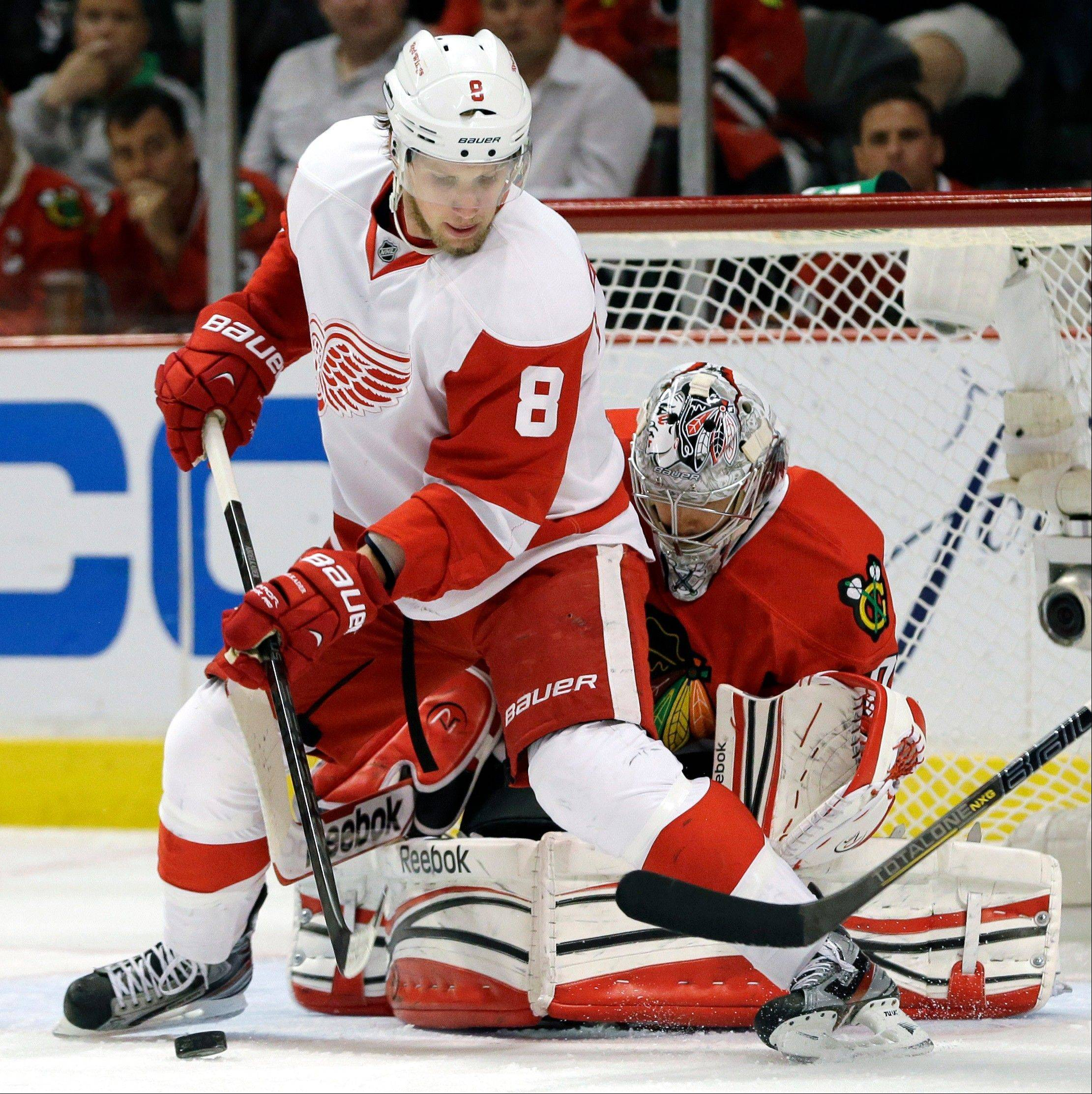 Detroit Red Wings' Justin Abdelkader (8) controls the puck against Chicago Blackhawks goalie Corey Crawford (50) during the first period of Game 5 of the NHL hockey Stanley Cup playoffs Western Conference semifinals in Chicago, Saturday, May 25, 2013.