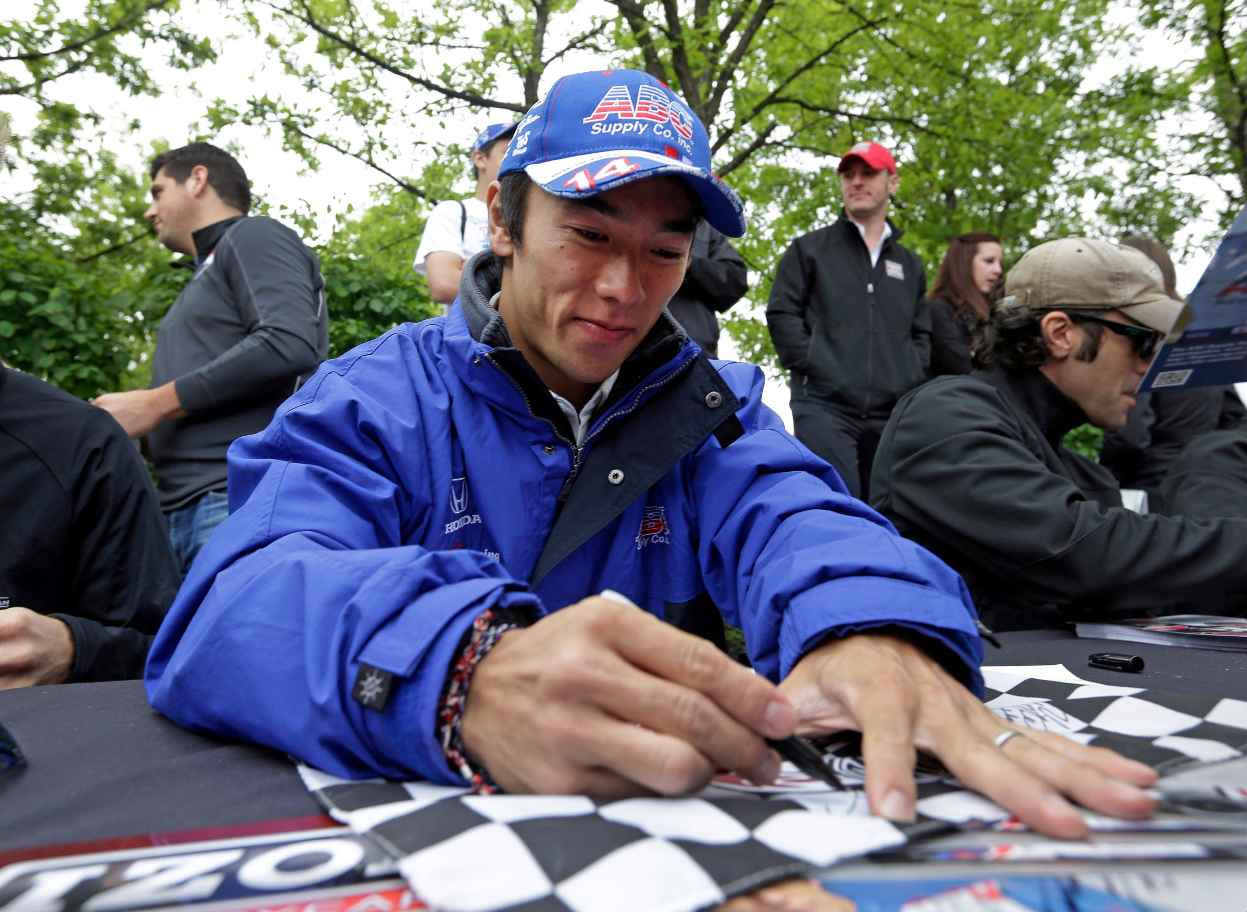 Takuma Sato, of Japan, signs a checkered flag for a fan during an autograph session before the public drivers meeting for the Indianapolis 500 auto race at the Indianapolis Motor Speedway in Indianapolis, Saturday, May 25, 2013.