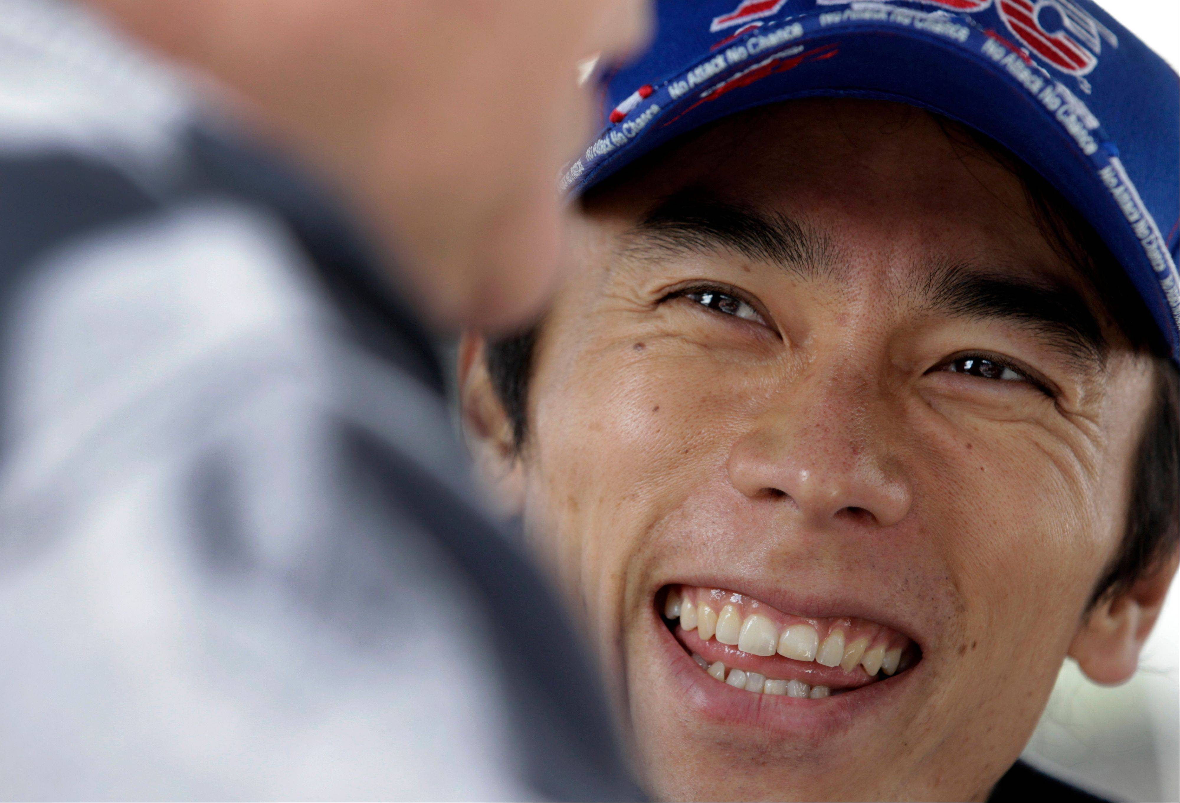 IndyCar driver Takuma Sato, of Japan, laughs as he talks with a member of his crew before the start of the final practice session for the Indianapolis 500 auto race at the Indianapolis Motor Speedway in Indianapolis, Friday, May 24, 2013.