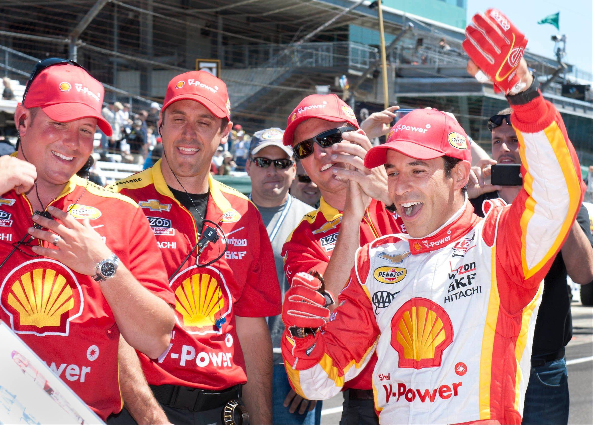 IndyCar driver Helio Castroneves, right, celebrates on the pit lane after winning the Pit Stop Challenge for a record sixth time at the Indianapolis Motor Speedway, Friday, May 24, 2013. (AP Photo/The Indianapolis Star, Gary Mook) NO SALES.