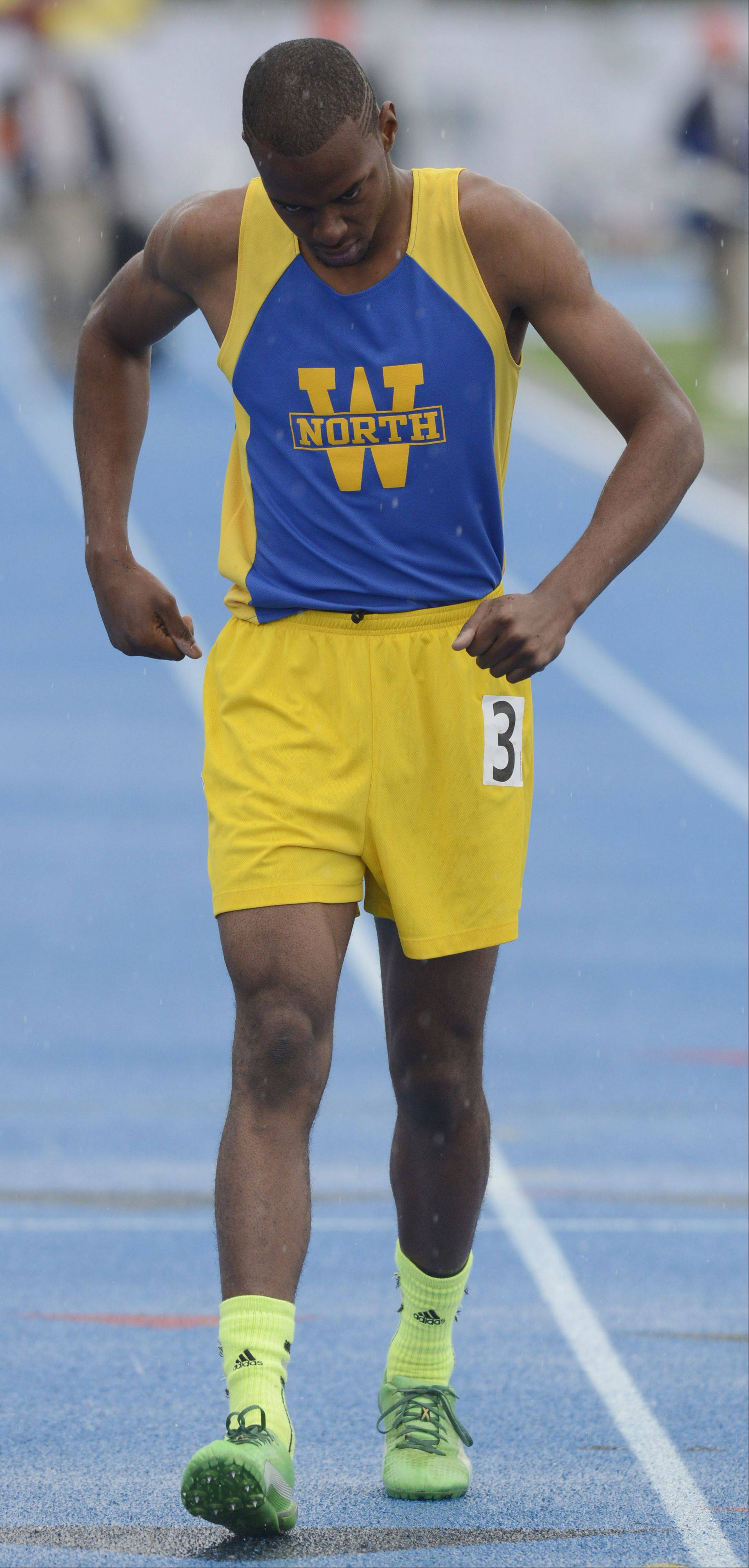 Despite being injured prior to the race, Wheaton North's Zach Gordon walks to the finish line in order to earn his medal in the 100-meter dash during the boys state track finals in Charleston Saturday.
