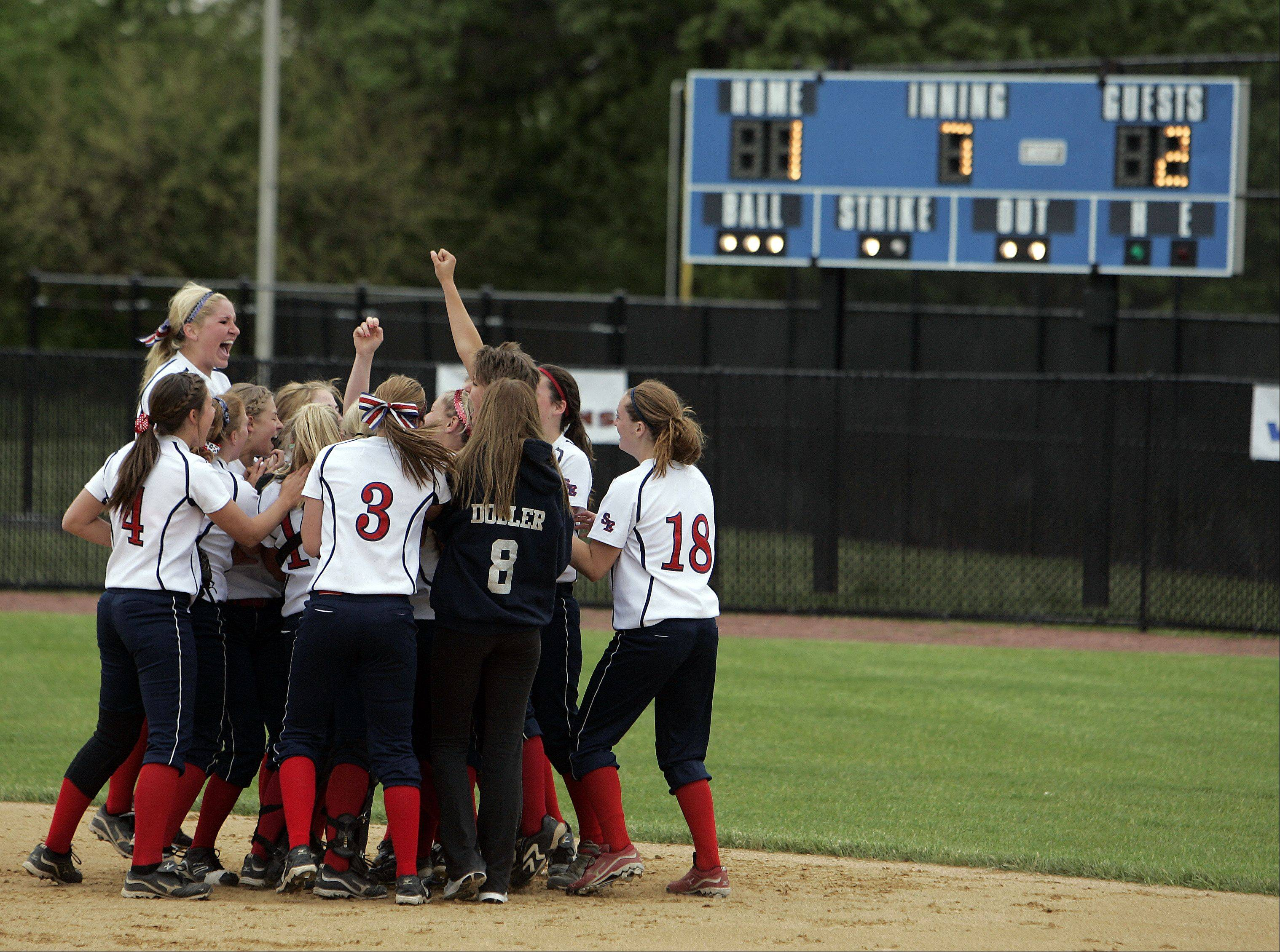 The South Elgin Storm celebrate their 2-1 victory over St. Charles North Saturday at the Class 4A regional softball final in St. Charles.