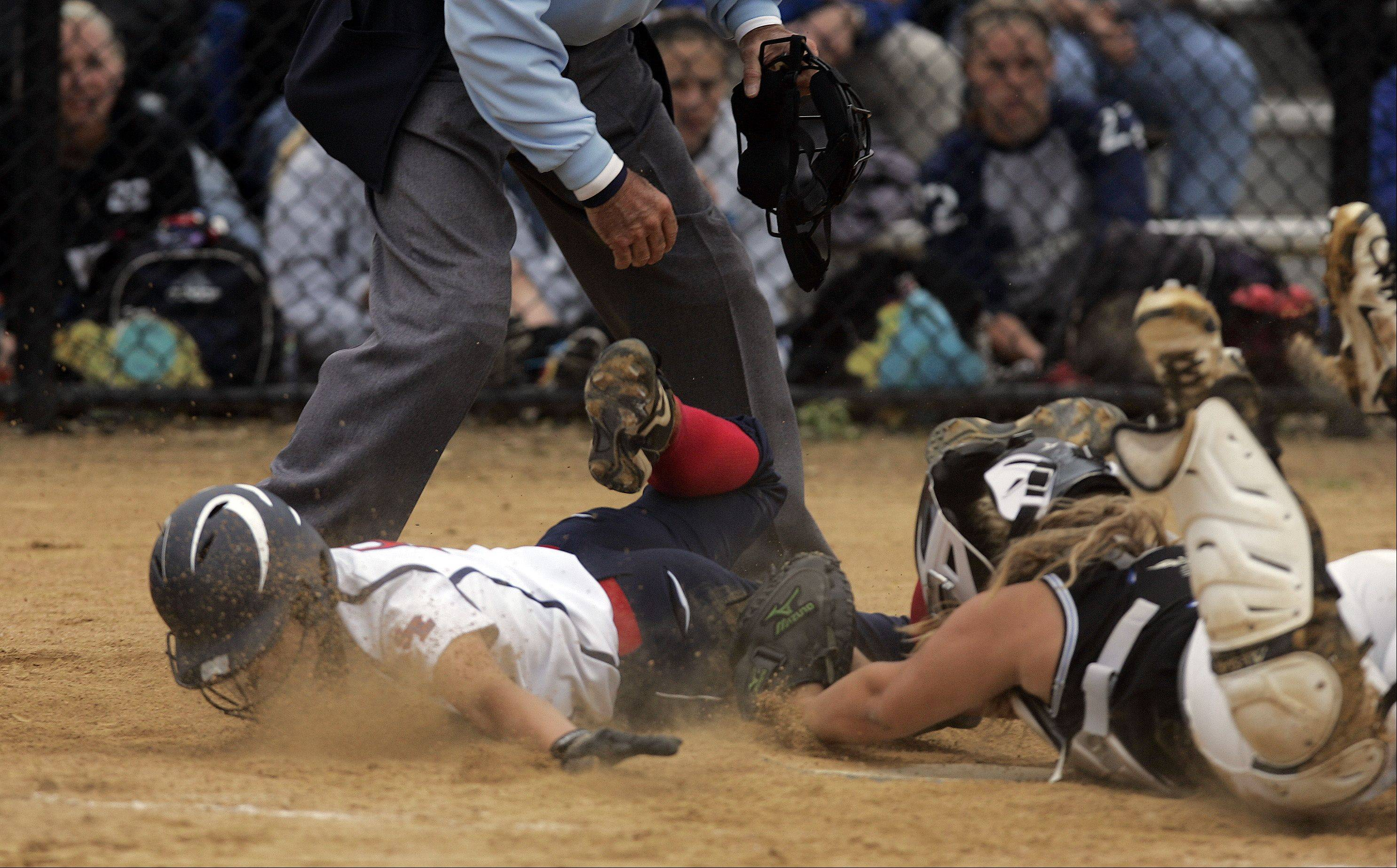 South Elgin's Victoria Watt slides safely under the tag of St. Charles North catcher Emily Brodner during the Class 4A regional softball final at St. Charles North Saturday.