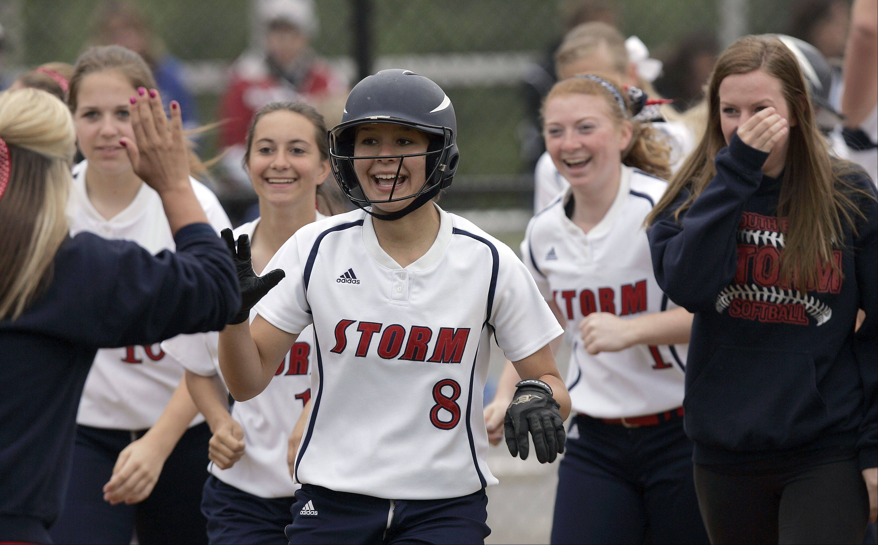 South Elgin's Victoria Watt(8) is greeted at the plate by her teammates after hitting a home run as the first batter in the game during the Class 4A regional softball final at St. Charles North Saturday.
