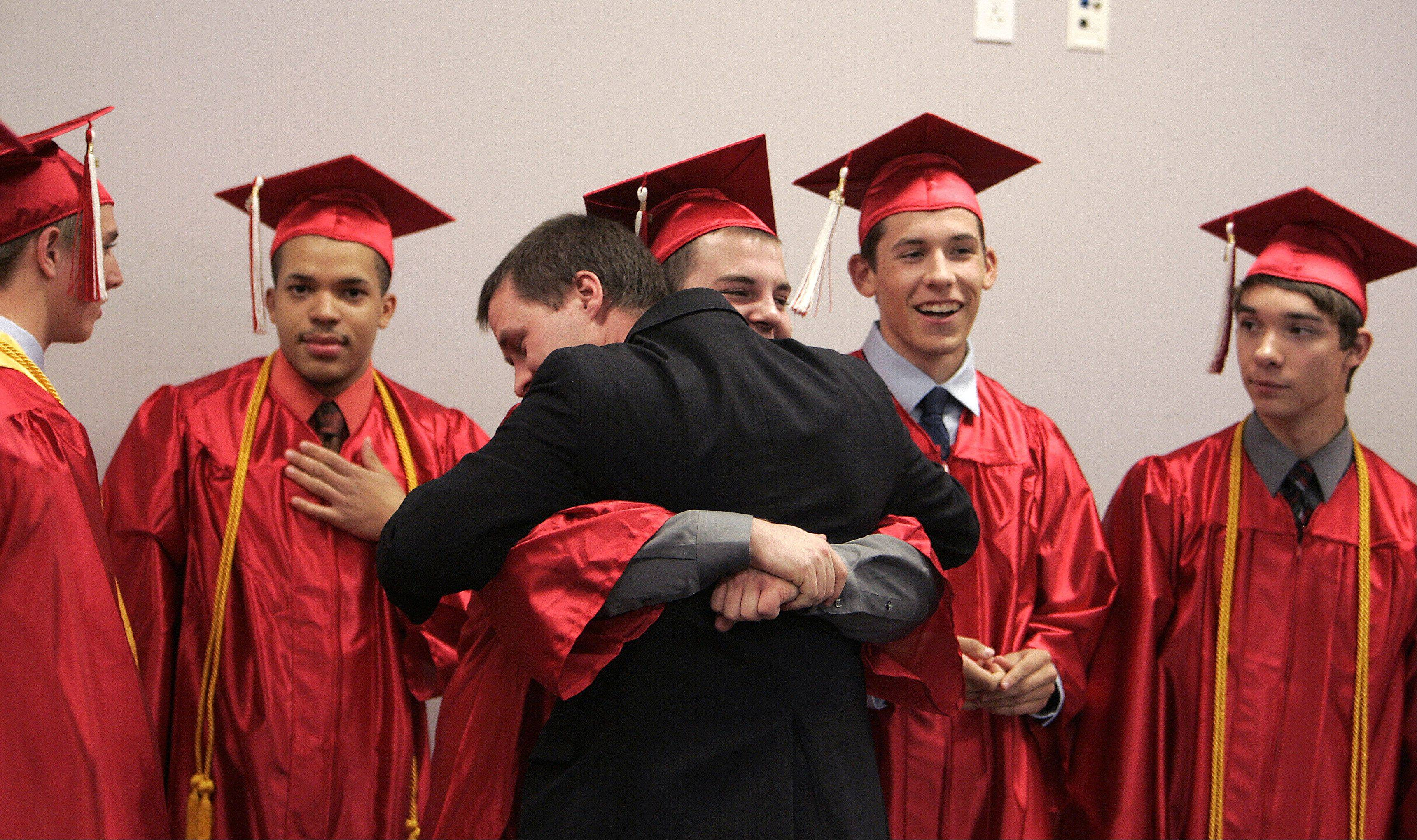 Aurora Christian Math teacher Bob Gorbold gets a giant bear hug from graduate Nick Larson as the students lined up for Aurora Christian�s commencement ceremony Sunday, May 26, 2013 in Aurora.