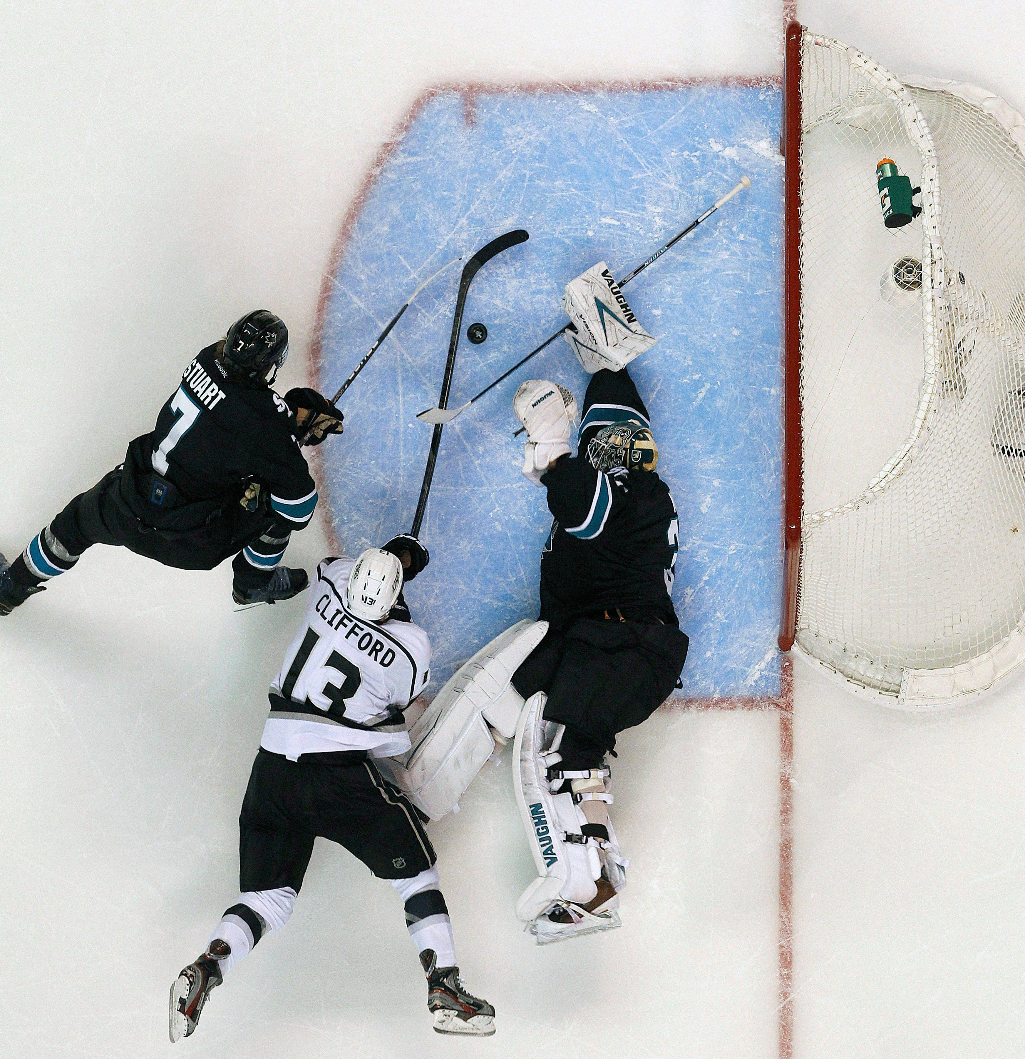 San Jose Sharks goalie Antti Niemi blocks a goal attempt by Los Angeles Kings left wing Kyle Clifford as Sharks defenseman Brad Stuart defends during the second period in Game 6 of their second-round NHL hockey Stanley Cup playoff series in San Jose, Calif., Sunday, May 26, 2013.