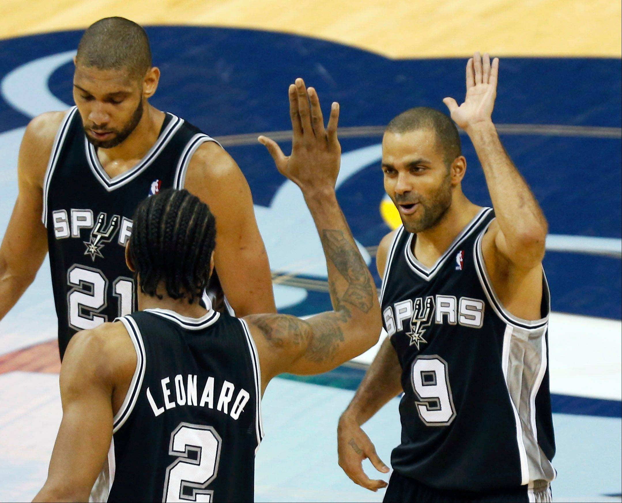 San Antonio Spurs' Kawhi Leonard (2) congratulates teammate Tony Parker (9), of France, after making a basket against the Memphis Grizzlies in overtime during Game 3 of the Western Conference finals NBA basketball playoff series, Saturday, May 25, 2013, in Memphis. The Spurs won 104-93 to lead the series 3-0. To the left is forward Tim Duncan (21). (AP Photo/Rogelio V. Solis)