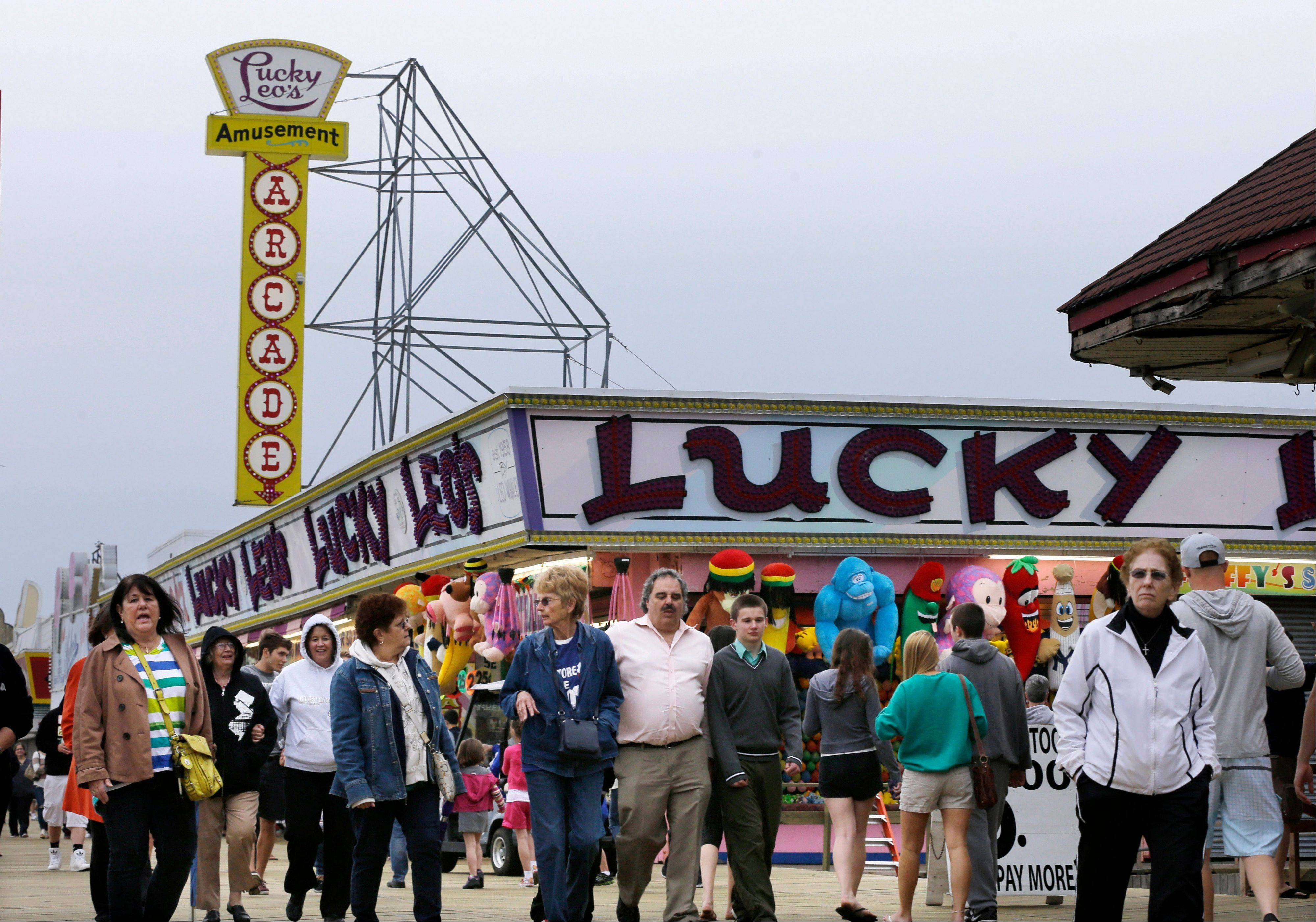 People walk past open attractions along the newly rebuilt boardwalk in Seaside Heights, N.J. Visitors to the Jersey shore will find many of their favorite beaches and boardwalks ready for summer, thanks to a massive rebuilding effort after Superstorm Sandy.