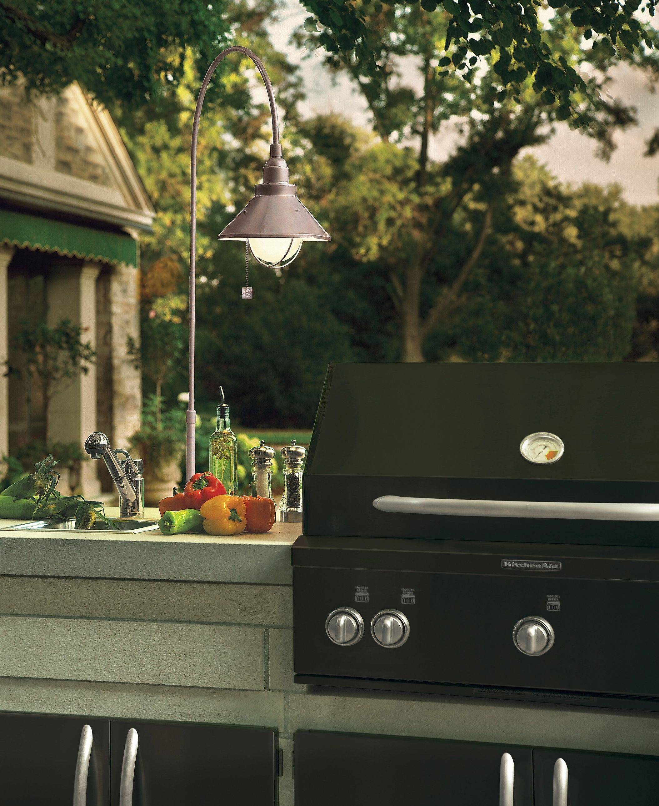 Specialty lighting, like this grill light at left, can ease the job of cooking in the dark. Other options are lights that illuminate the insides of drawers in outdoor kitchens and provide backlight for countertops.