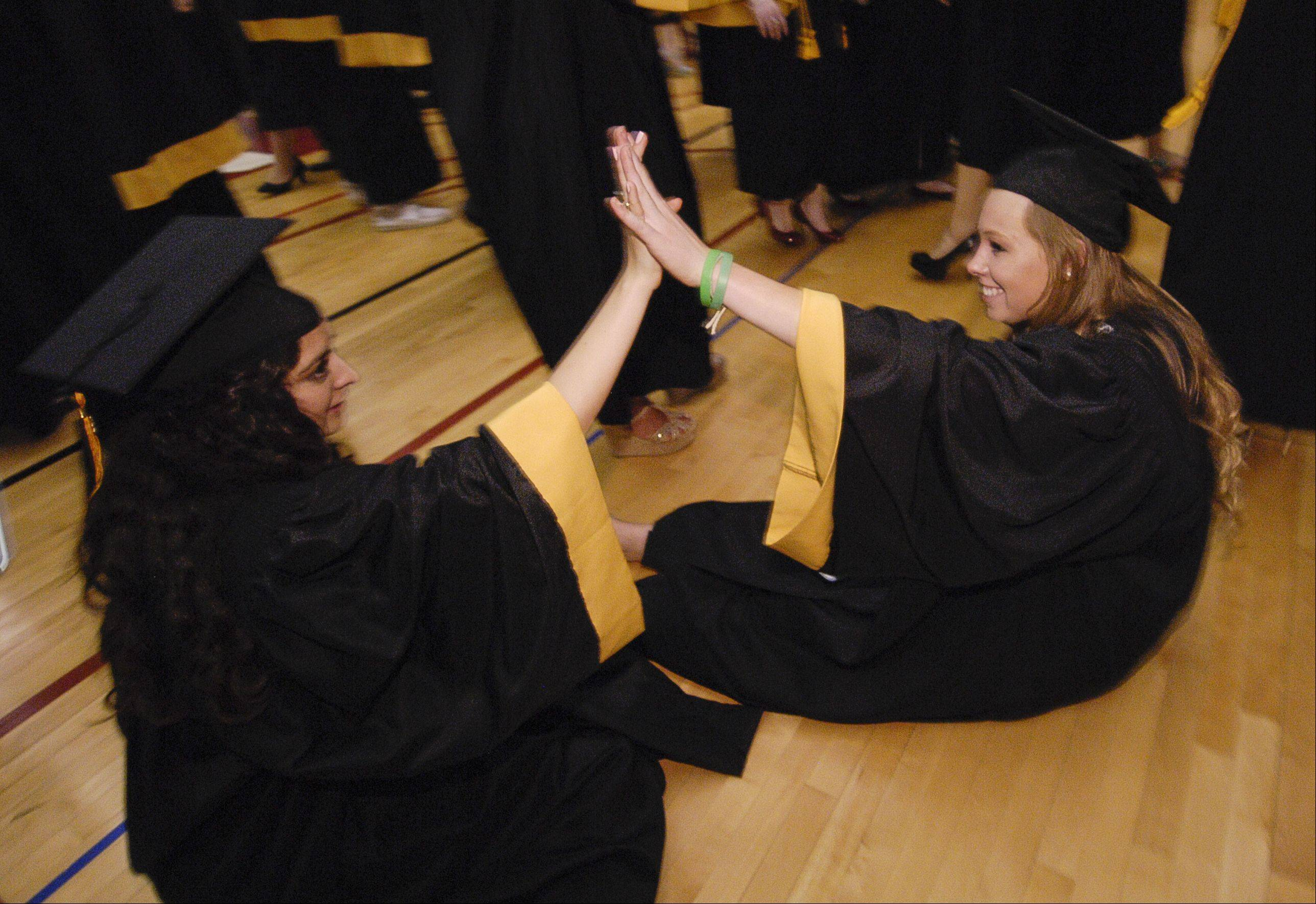 Carolyn O'Neill and Amy Nealon high-five each other before the Metea Valley High School graduation on Sunday, May 26 at the NIU Convocation Center in DeKalb.