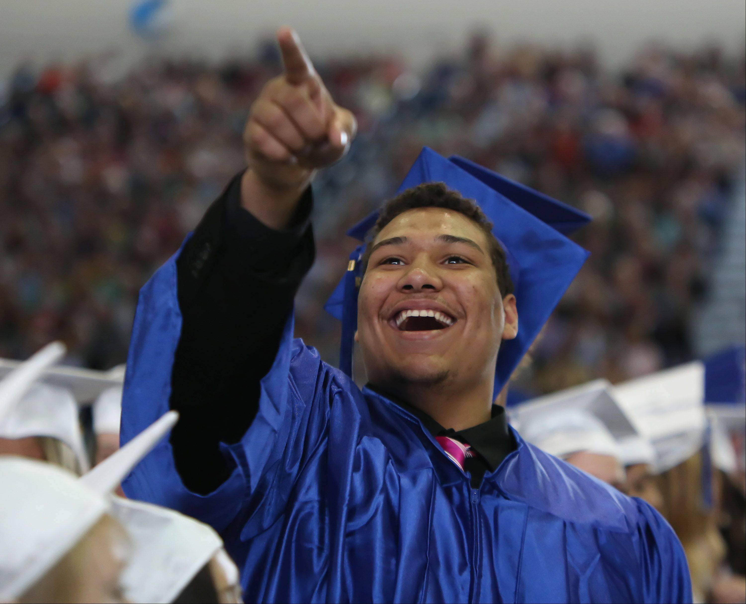 Apollo Millon smiles as he points up to family members during the Lake Zurich High School graduation ceremony on Sunday. There were 542 seniors graduating this year at the school.