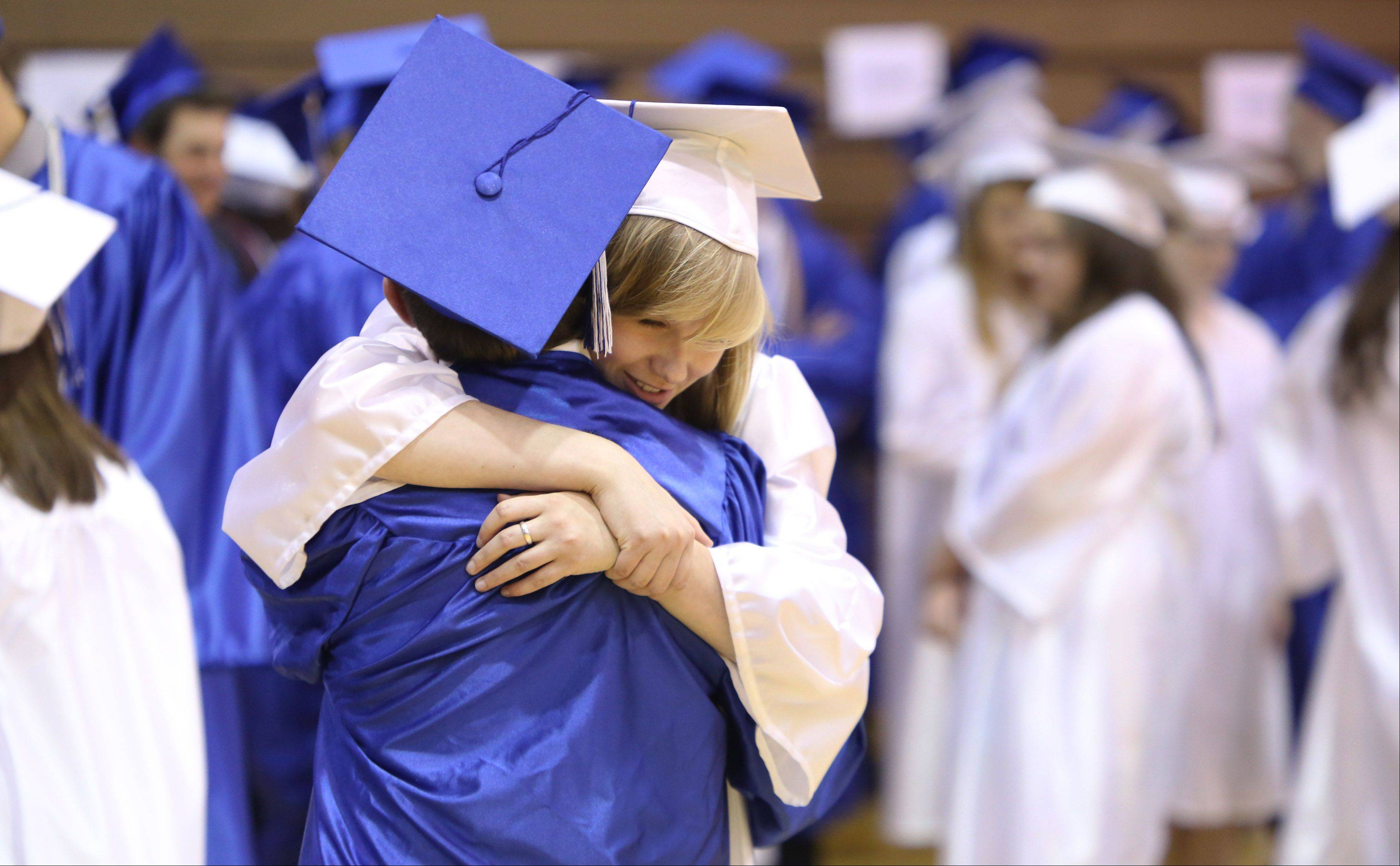 Katie Dunbar hugs Giacomo Black during the Lake Zurich High School graduation ceremony on Sunday. There were 542 seniors graduating this year at the school.