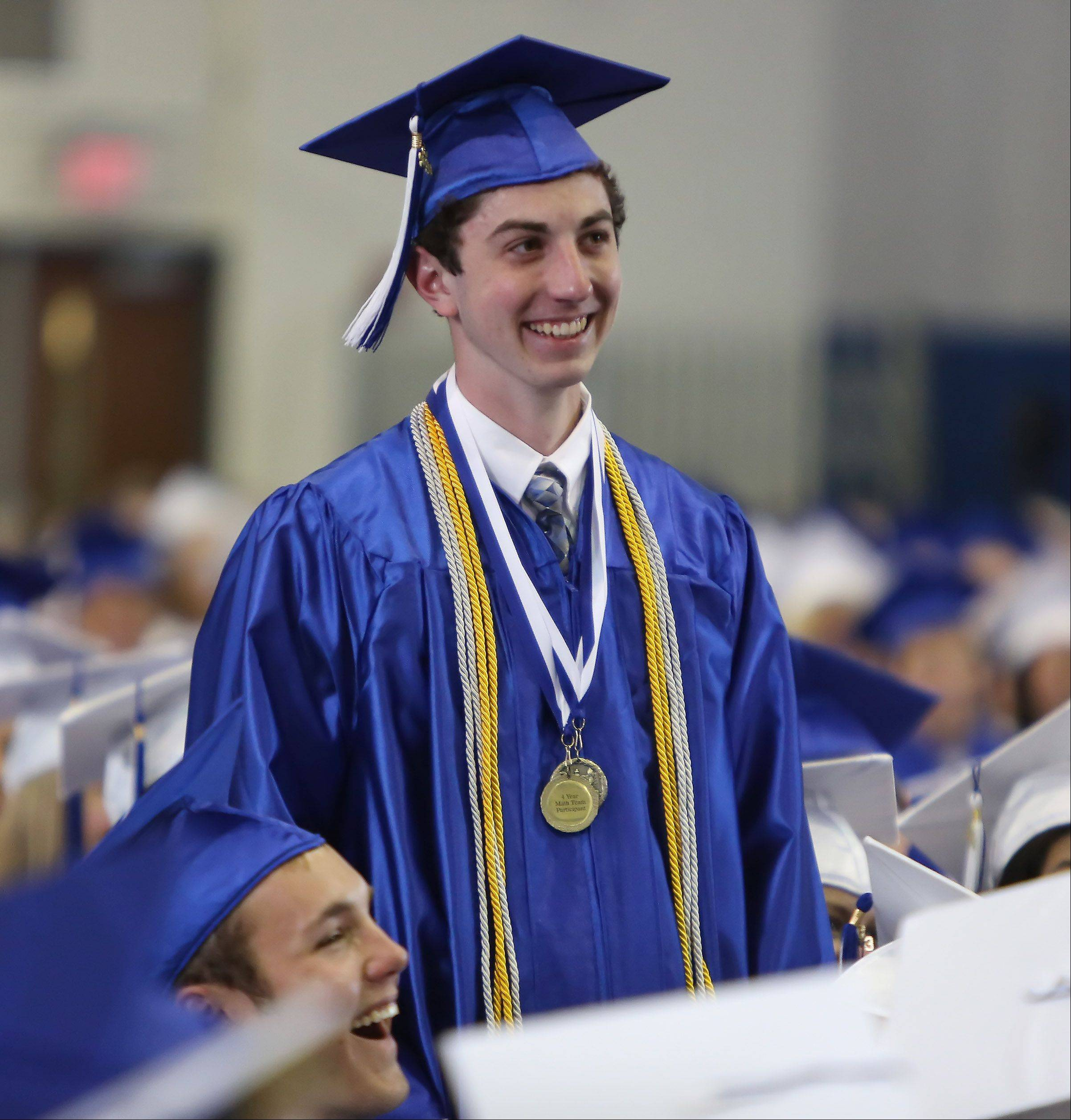 Mark Noll is asked to stand by faculty speaker Chris Bennett during the Lake Zurich High School graduation ceremony on Sunday. Noll was recognized as the only senior at the school who is a National Merit Scholar and the only one who raises chickens.