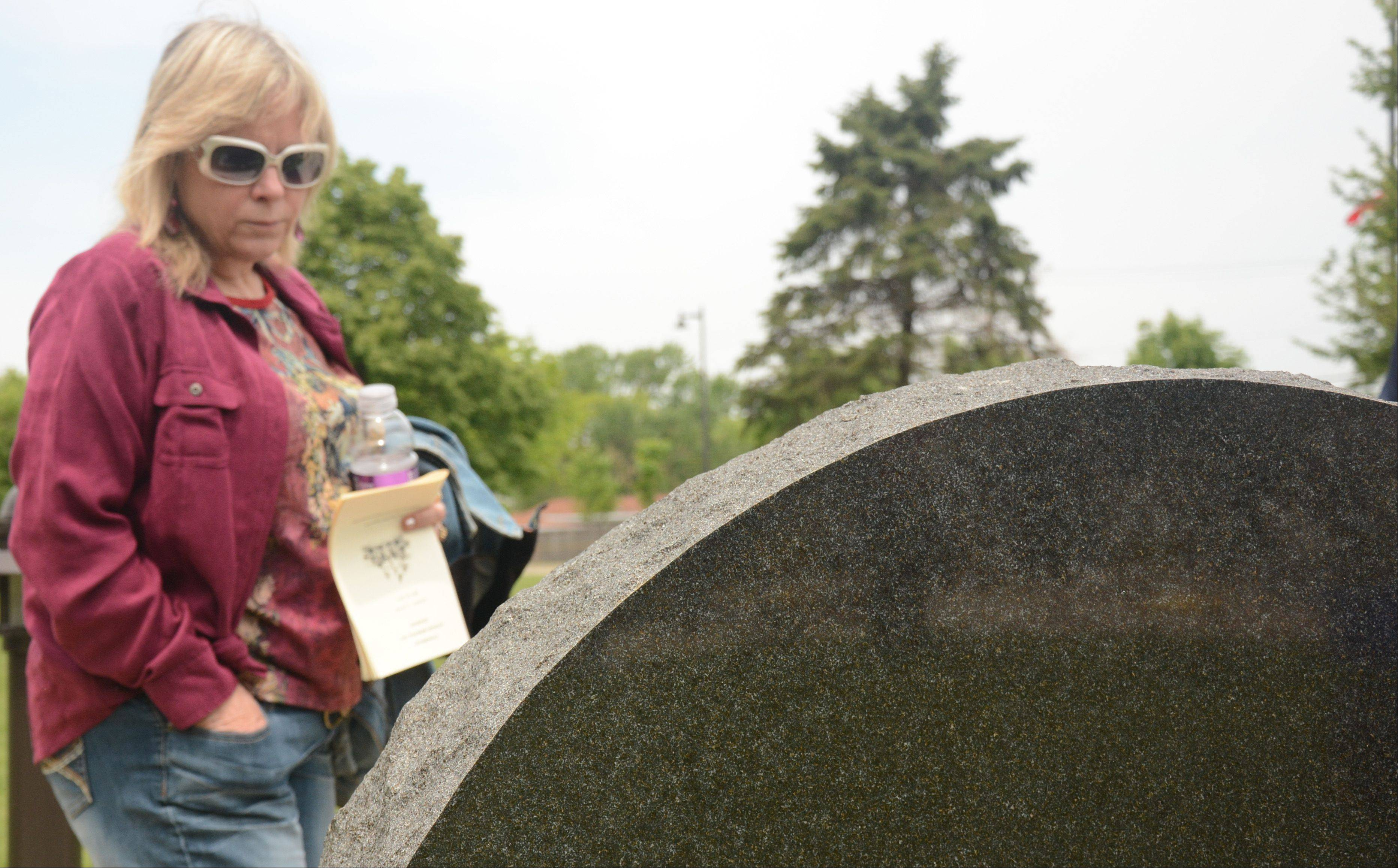Sue Davis pauses to look at a monument during the Streamwood Memorial Day ceremony Sunday.