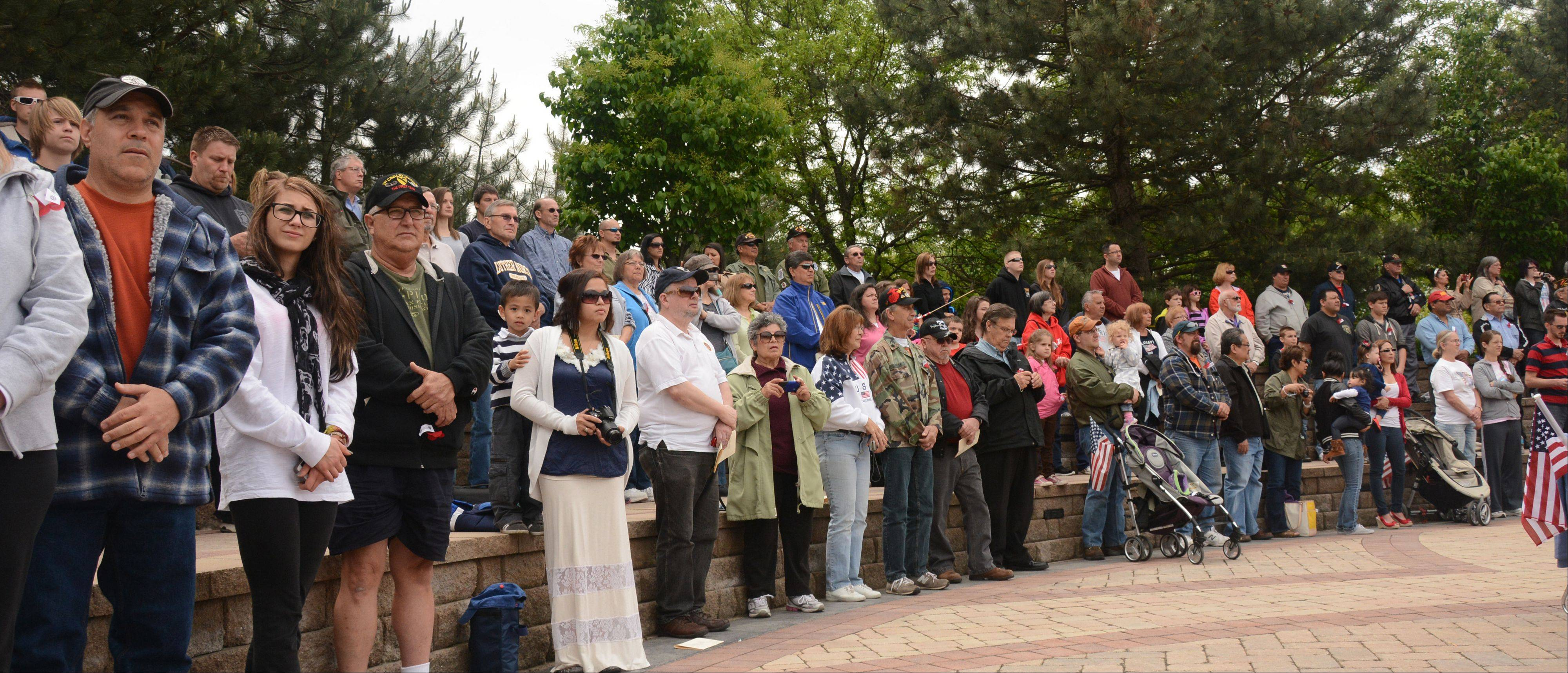A large crowd silently watches the Streamwood Memorial Day ceremony Sunday. The ceremony included speeches, flag presentations, a moment of silence, a 21-gun salute, the playing of Taps, and the placement of wreaths at the memorial's monoliths.