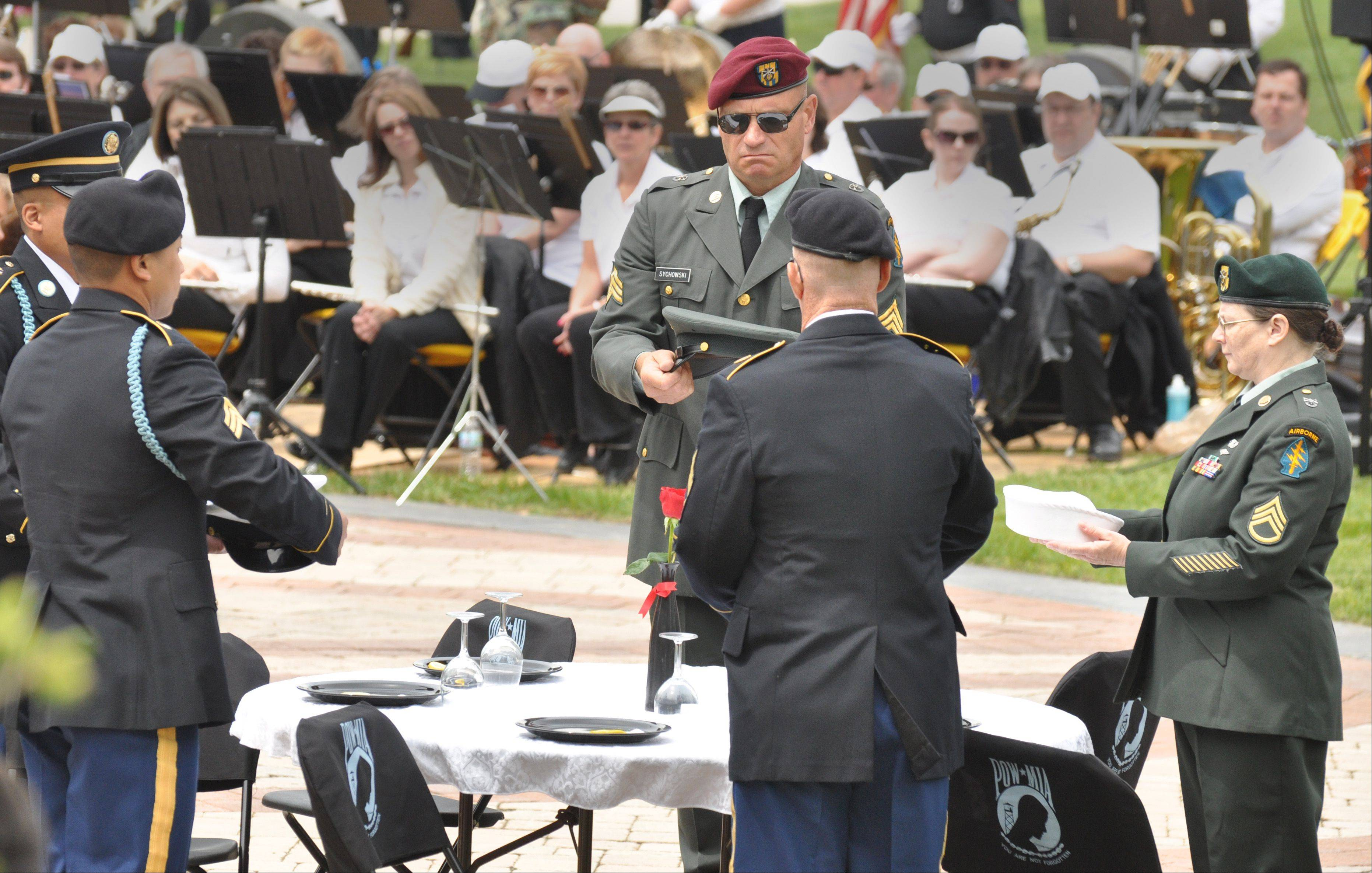 "An ""empty table"" ceremony is performed in honor of prisoners of war and soldiers missing in action during Streamwood's Memorial Day ceremony Sunday."
