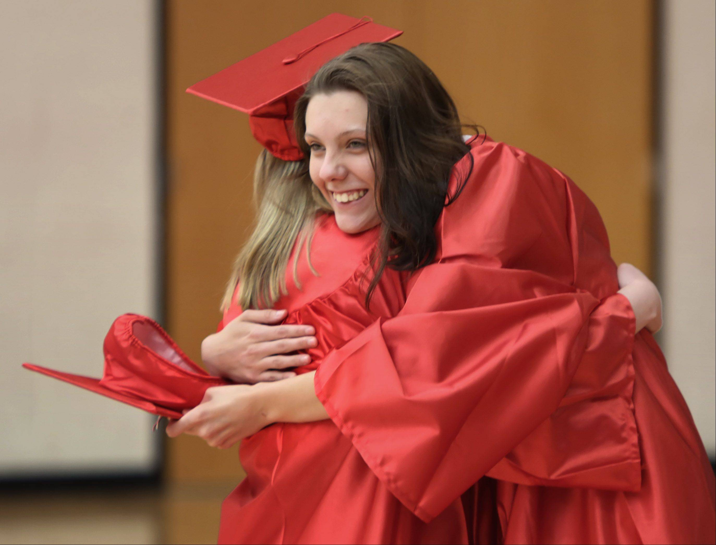 Carol Schoiber, right, hugs her friend Taylor Spradling during the Grant High School graduation ceremony on Sunday. There were 399 seniors graduating this year at the school.