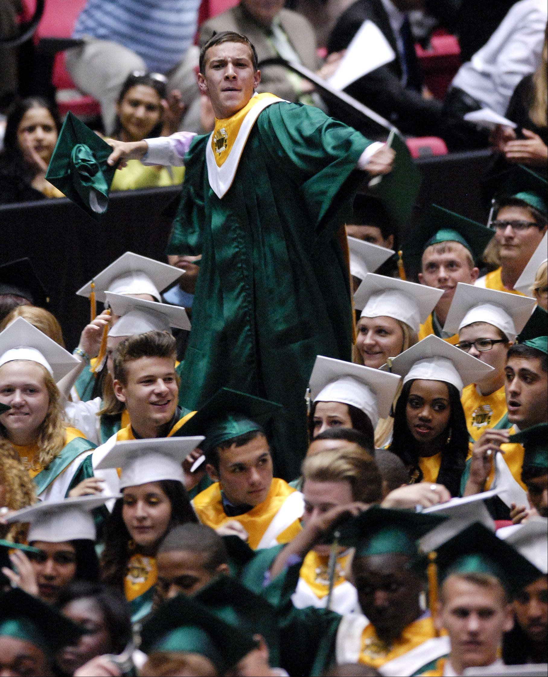 Waubonsie Valley High School graduate climbs up on his chair to toss his cap at the end of the Waubonsie Valley High School graduation on Sunday, May 26 at the NIU Convocation Center in DeKalb.