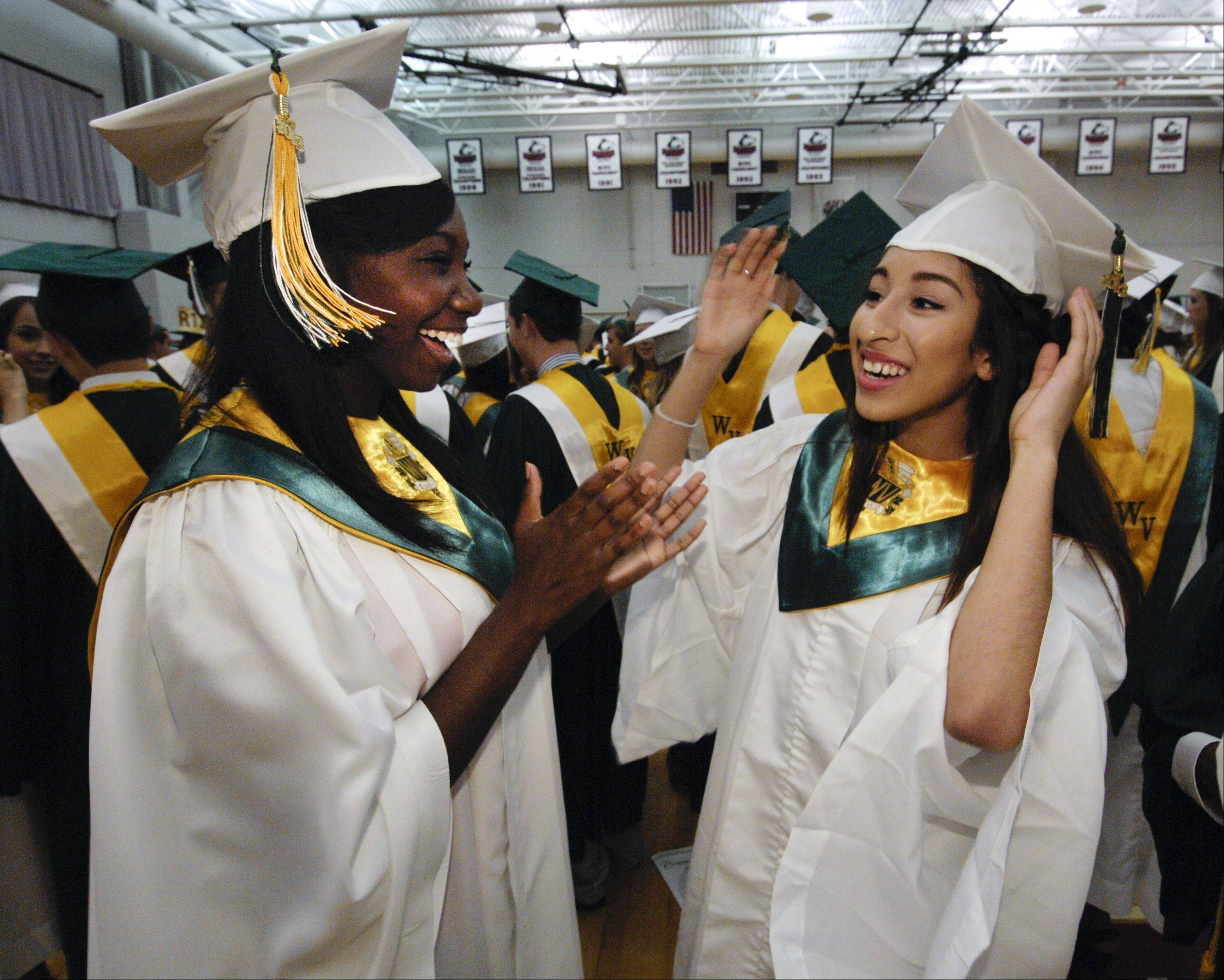 Savannah Price and Melody Sanchez greet each other before the start of the Waubonsie Valley High School graduation on Sunday, May 26 at the NIU Convocation Center in DeKalb.