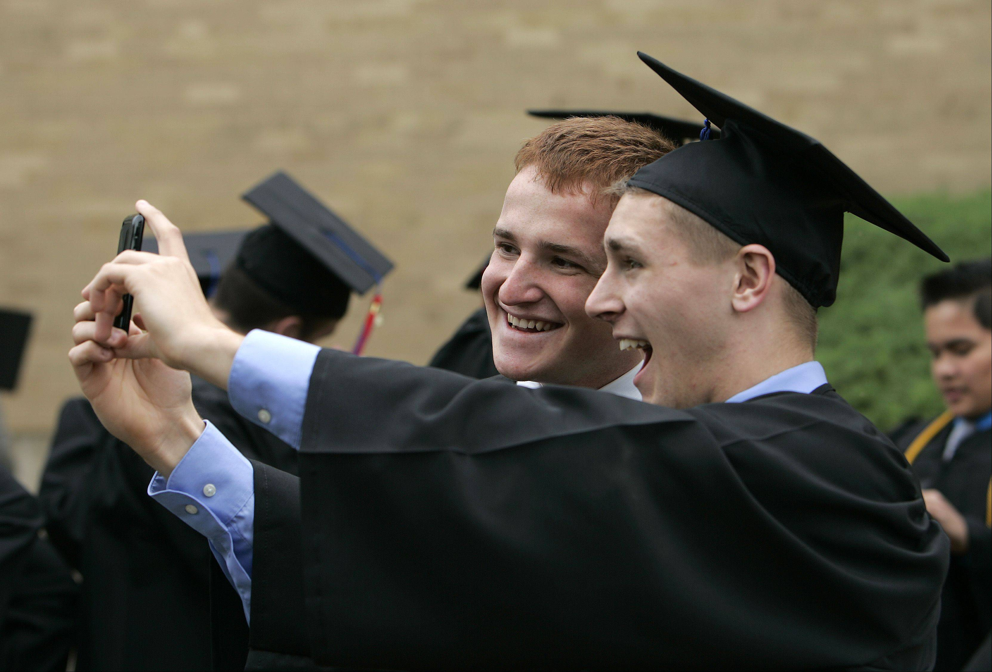 Brian Winkel, left, and Stuart Kofron, both of Batavia, snap a quick cellphone picture prior to Marmion Academy's 79th commencement exercises Sunday, May 26, 2013 in Aurora.
