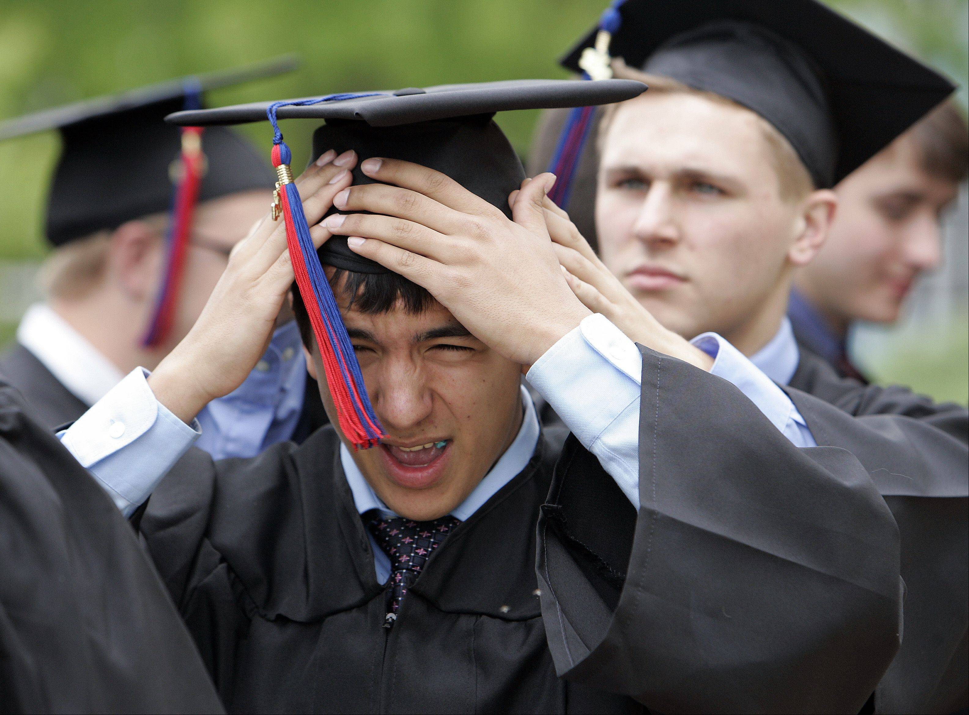 Alex Lopez of Lisle gets a helping hand with his mortarboard before Marmion Academy's 79th commencement exercises Sunday, May 26, 2013 in Aurora.