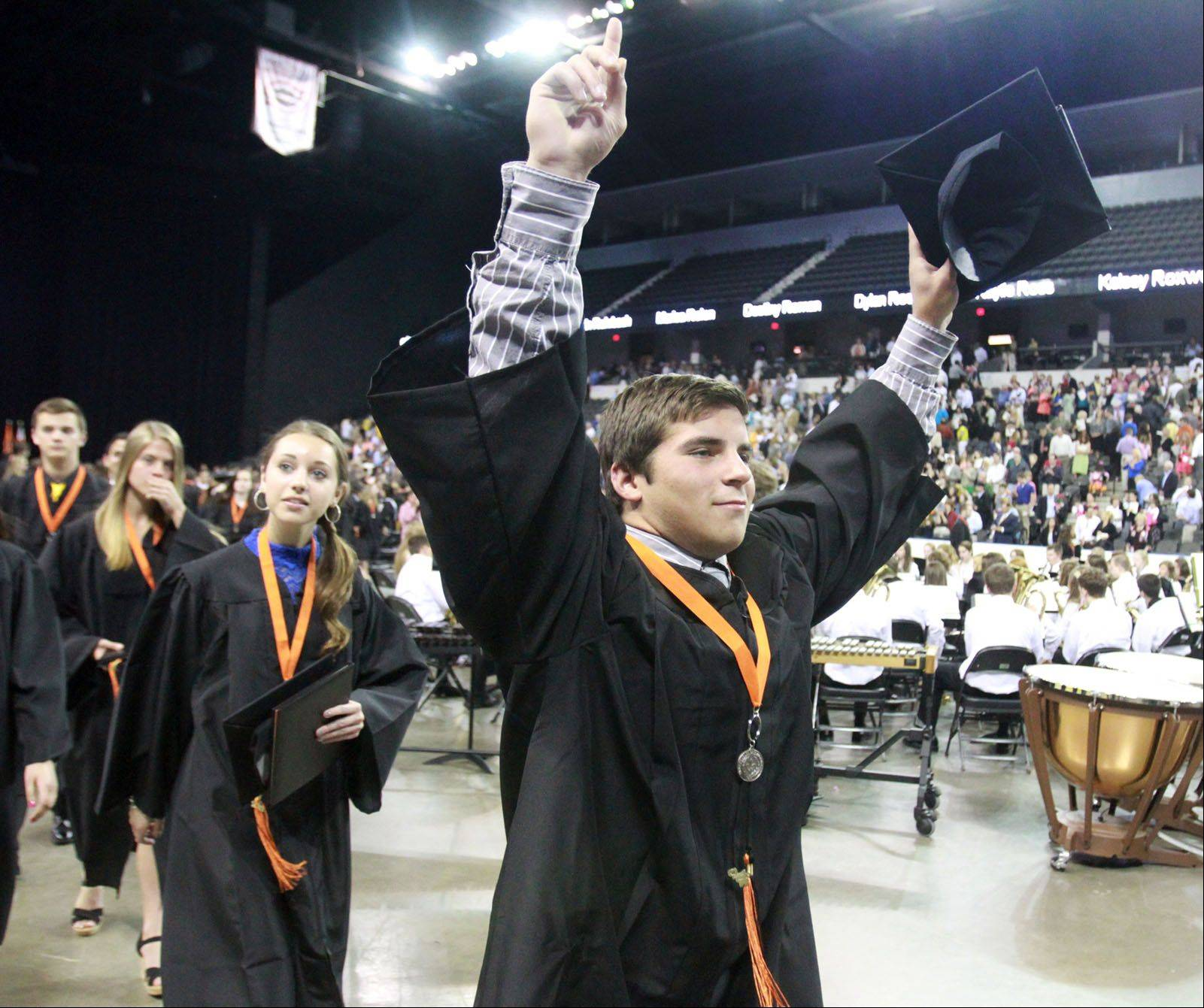 St. Charles East High School graduate Sam Malone raises his cap as he leads student marching out of the school's commencement ceremony at the Sears Centre in Hoffman Estates on Sunday, May 26, 2013.
