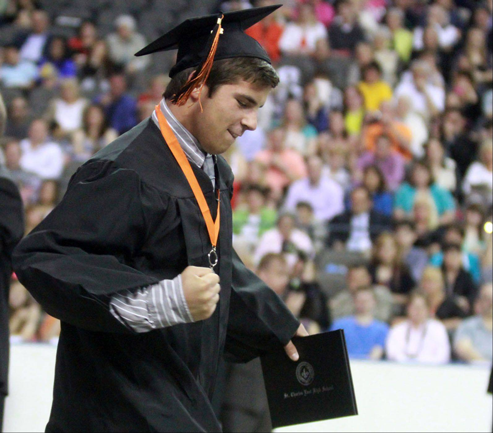 St. Charles East High School graduate Sam Malone celebrates receiving his diploma as he walks offstage during the school's commencement ceremony at the Sears Centre in Hoffman Estates on Sunday, May 26, 2013.