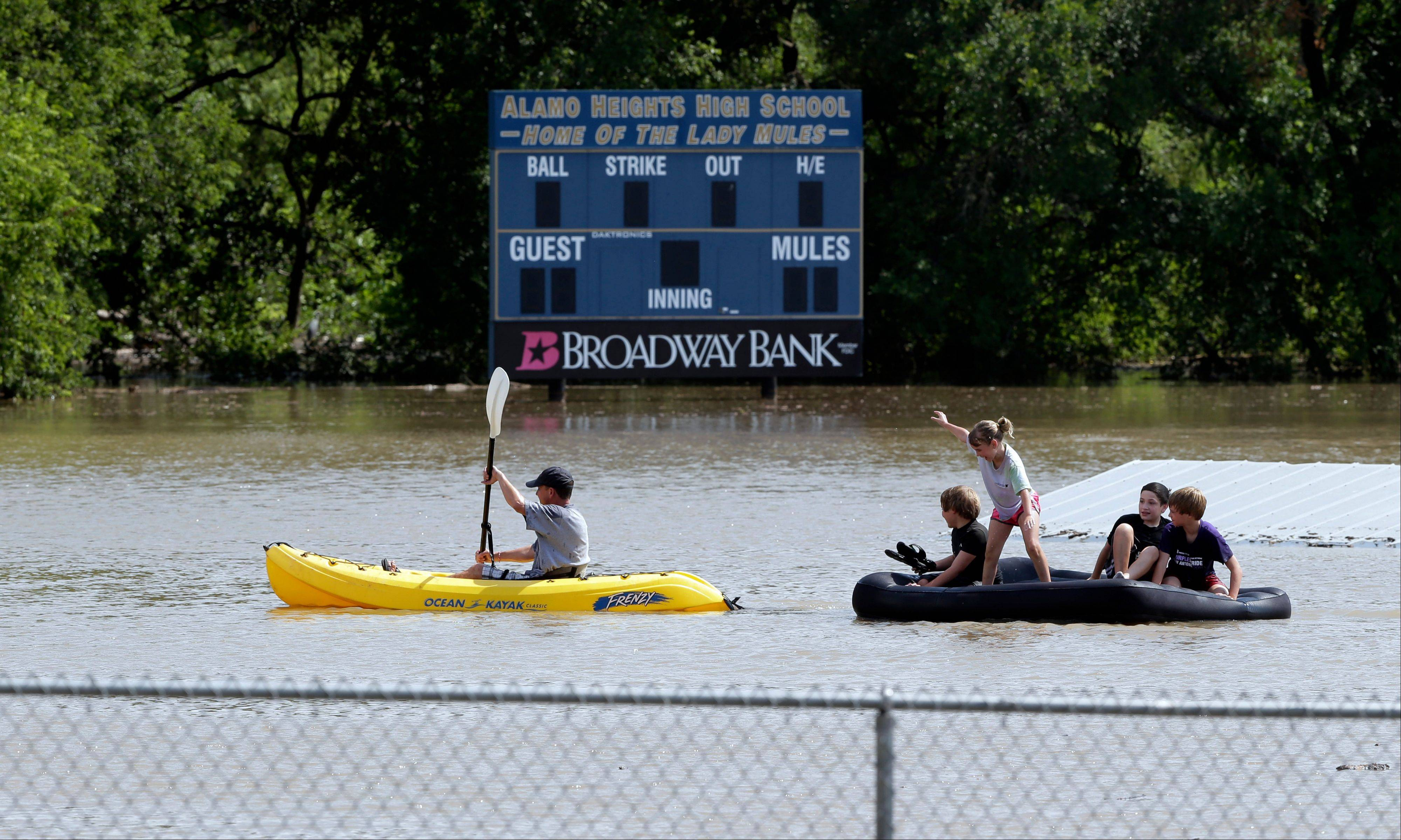 A kayaker pulls a raft with children around a flooded baseball park in San Antonio, Saturday, May 25, 2013, in San Antonio. San Antonio International Airport recorded more than nine inches of rain since midnight.
