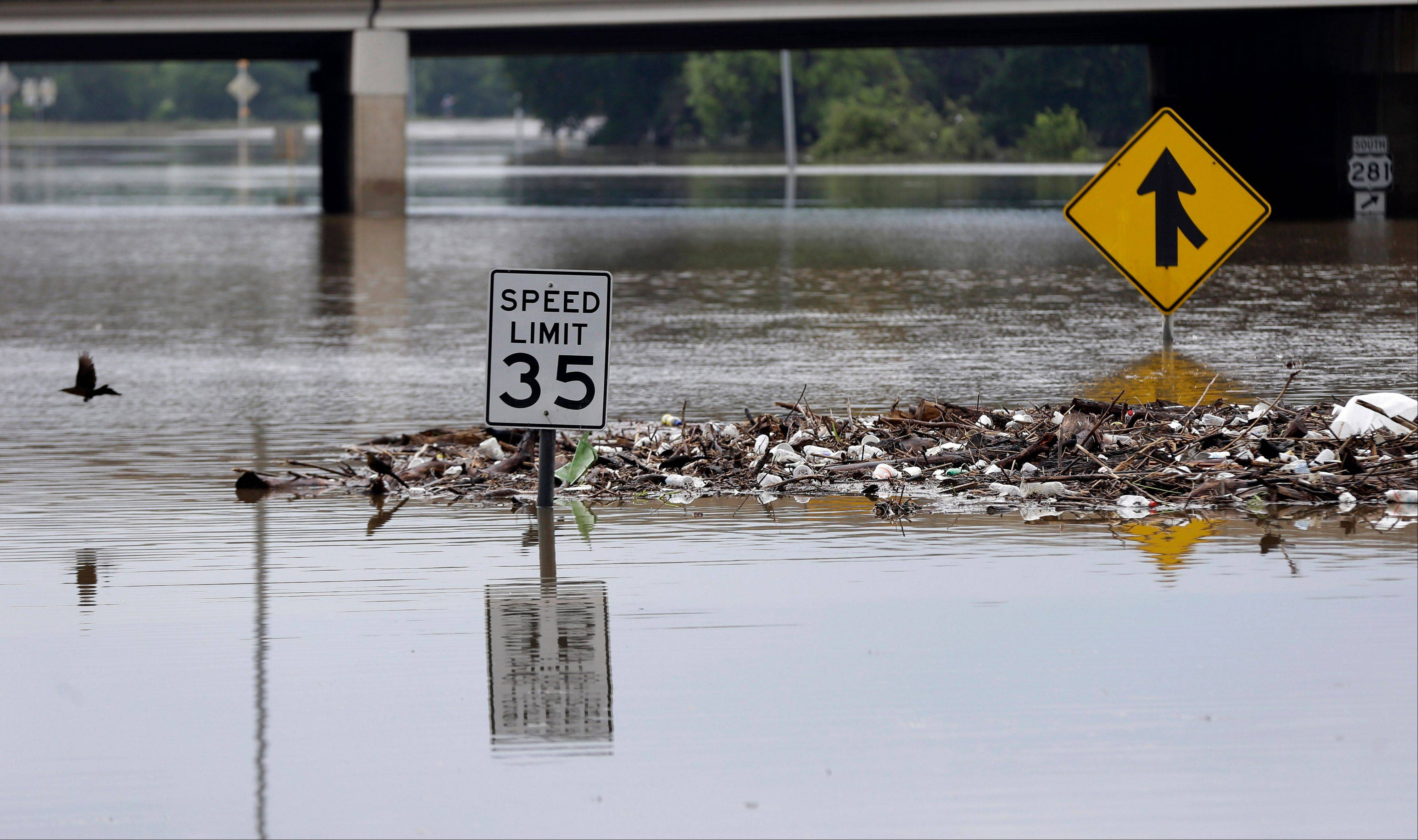 Debris gathers around street signs on a flooded road, Sunday, May 26, 2013, in San Antonio. Heavy rains and flooding are being blamed for at least two deaths in San Antonio.