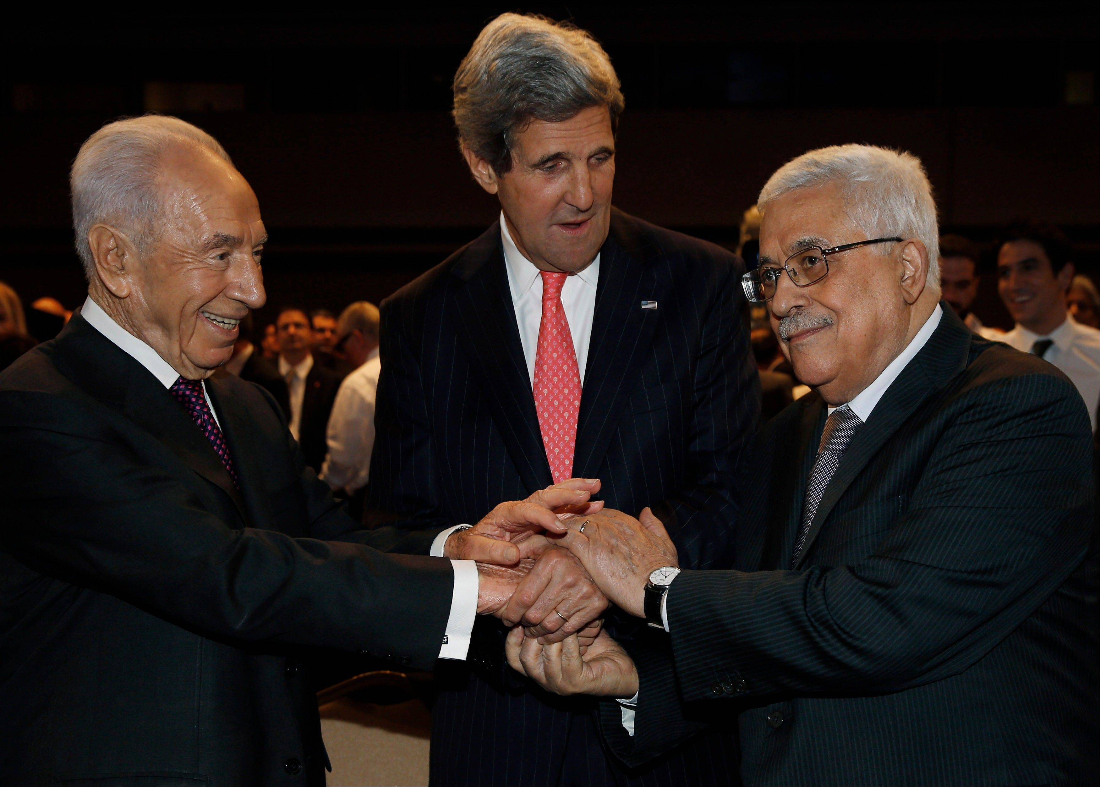 U.S. Secretary of State John Kerry, center, Israeli President Shimon Peres, right, and Palestinian President Mahmoud Abbas all shake hands during the World Economic Forum on the Middle East and North Africa at the King Hussein Convention Centre at the Dead Sea in Jordan Sunday May 26, 2013.
