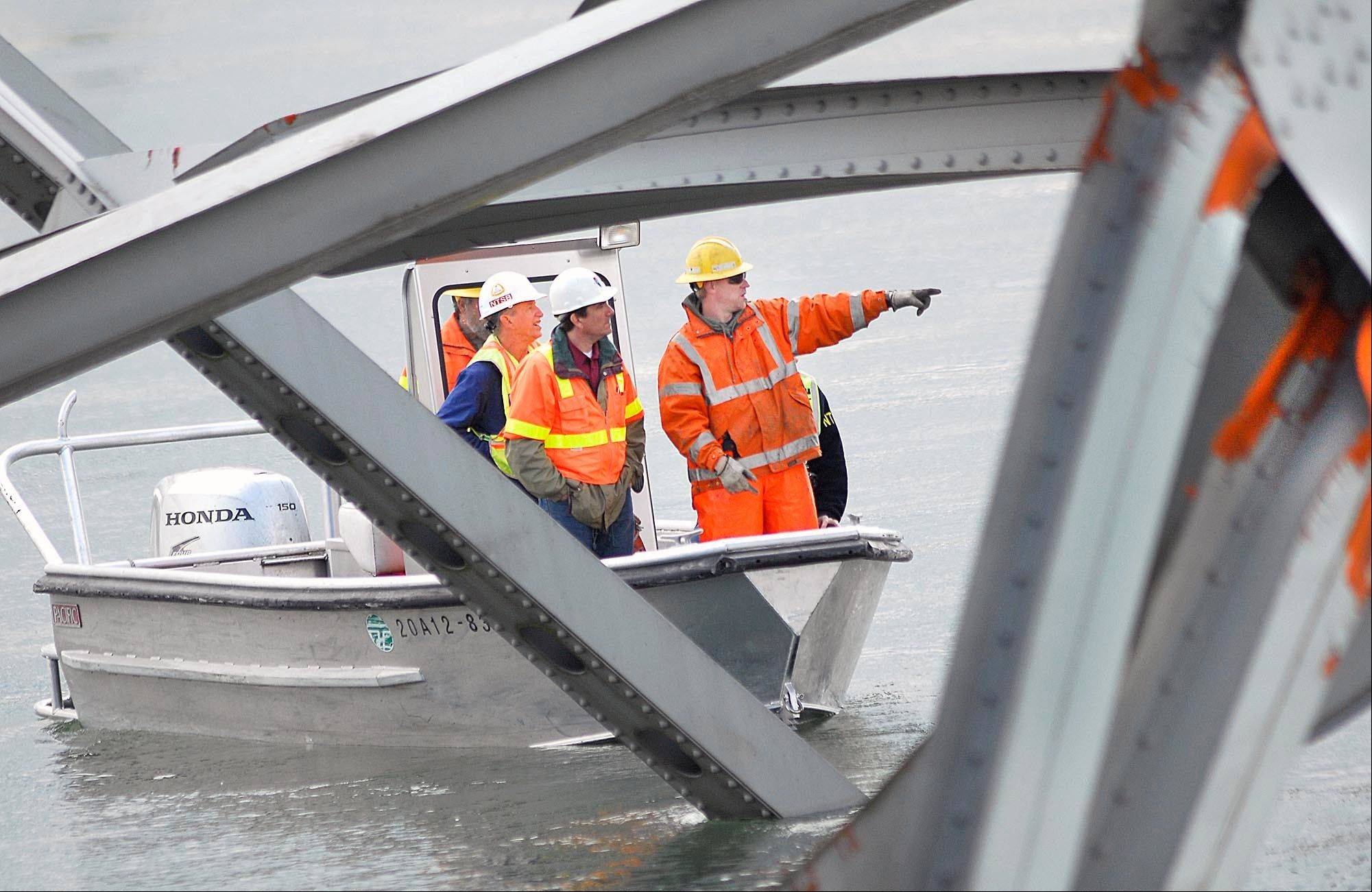 A crew from the National Transportation Safety Board inspects a section of the Skagit River Bridge, Saturday, May 25, 2013 in Mount Vernon, Wash. The chairman of the National Transportation Safety Board said Saturday the bridge collapse in Washington state is a wake-up call for the nation.