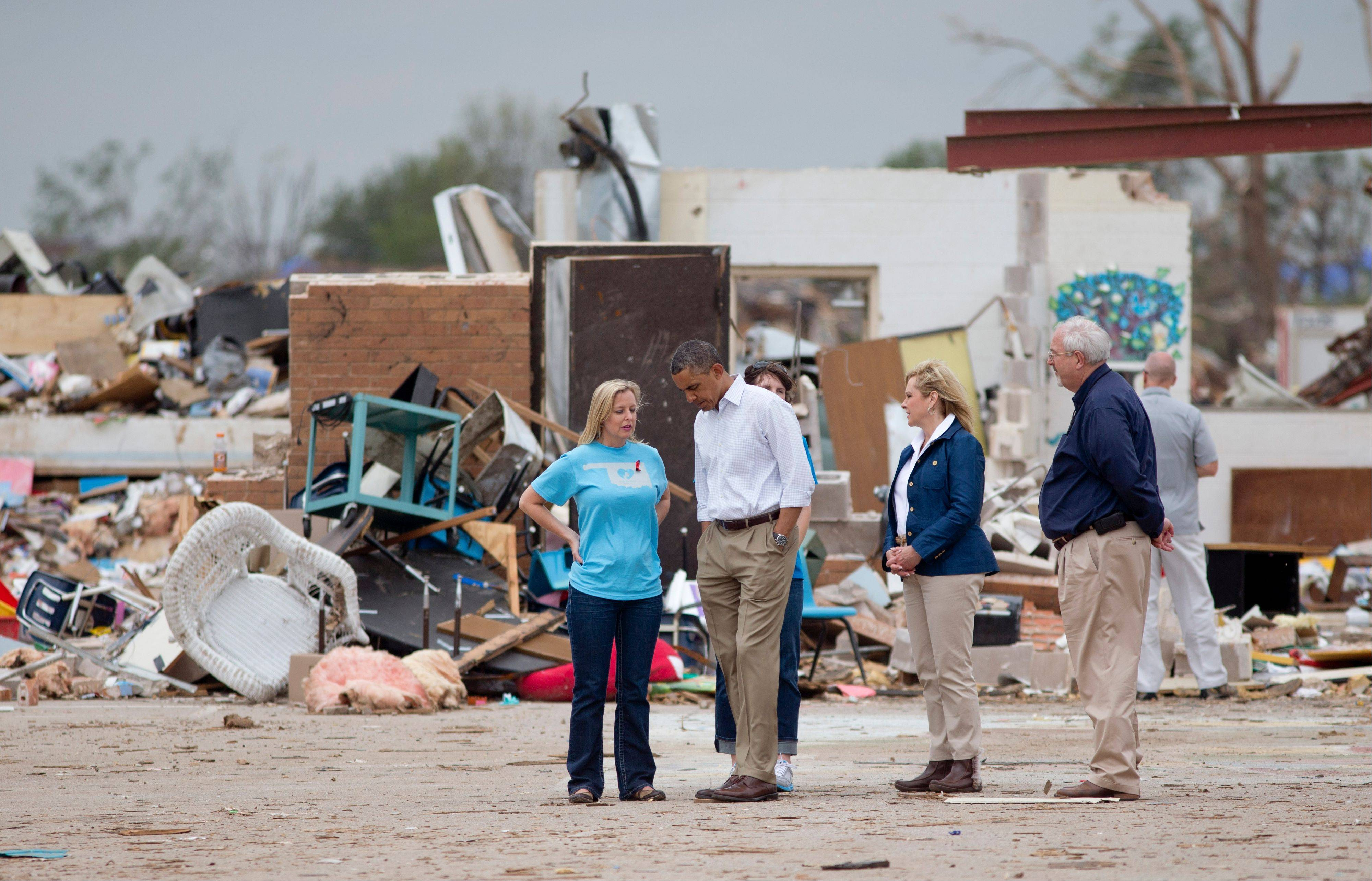 President Barack Obama listens to Plaza Towers Elementary School principal Amy Simpson, left, with Oklahoma Gov. Mary Fallin, second from right, and FEMA administrator W. Craig Fugate, right as he views the devastation of the Plaza Towers Elementary School, Sunday, May 26, 2013, in Moore, Okla., after the massive tornado and severe weather the we before.