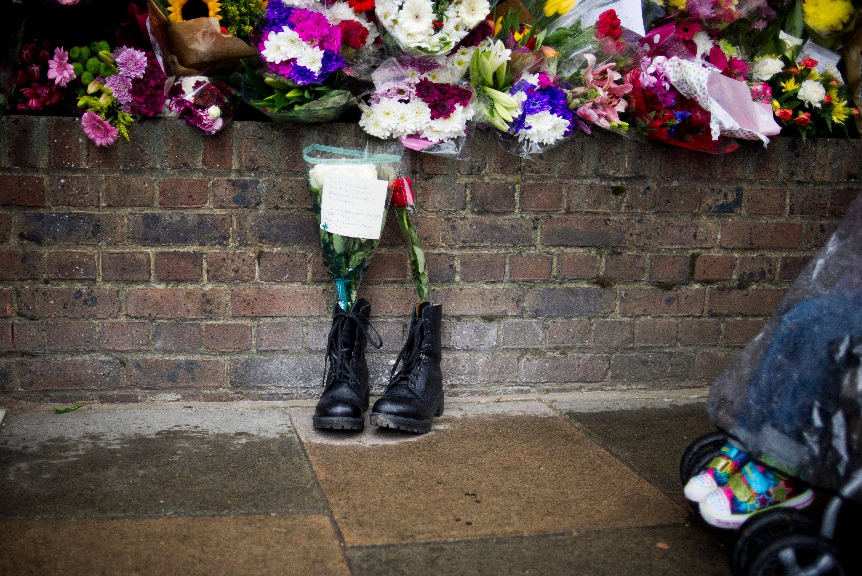 In this Friday, May 24, 2013 file photo, military boots are laid in tribute outside the Woolwich Barracks, in London, in response to the bloody attack on Wednesday when a British soldier was killed in the nearby street. Counterterrorism police on Saturday were questioning a friend of Michael Adebolajo, one of two suspects in the savage killing of British soldier Lee Rigby. The friend, Abu Nusaybah, was arrested immediately after he gave a television interview telling his story about how Adebolajo may have become radicalized.