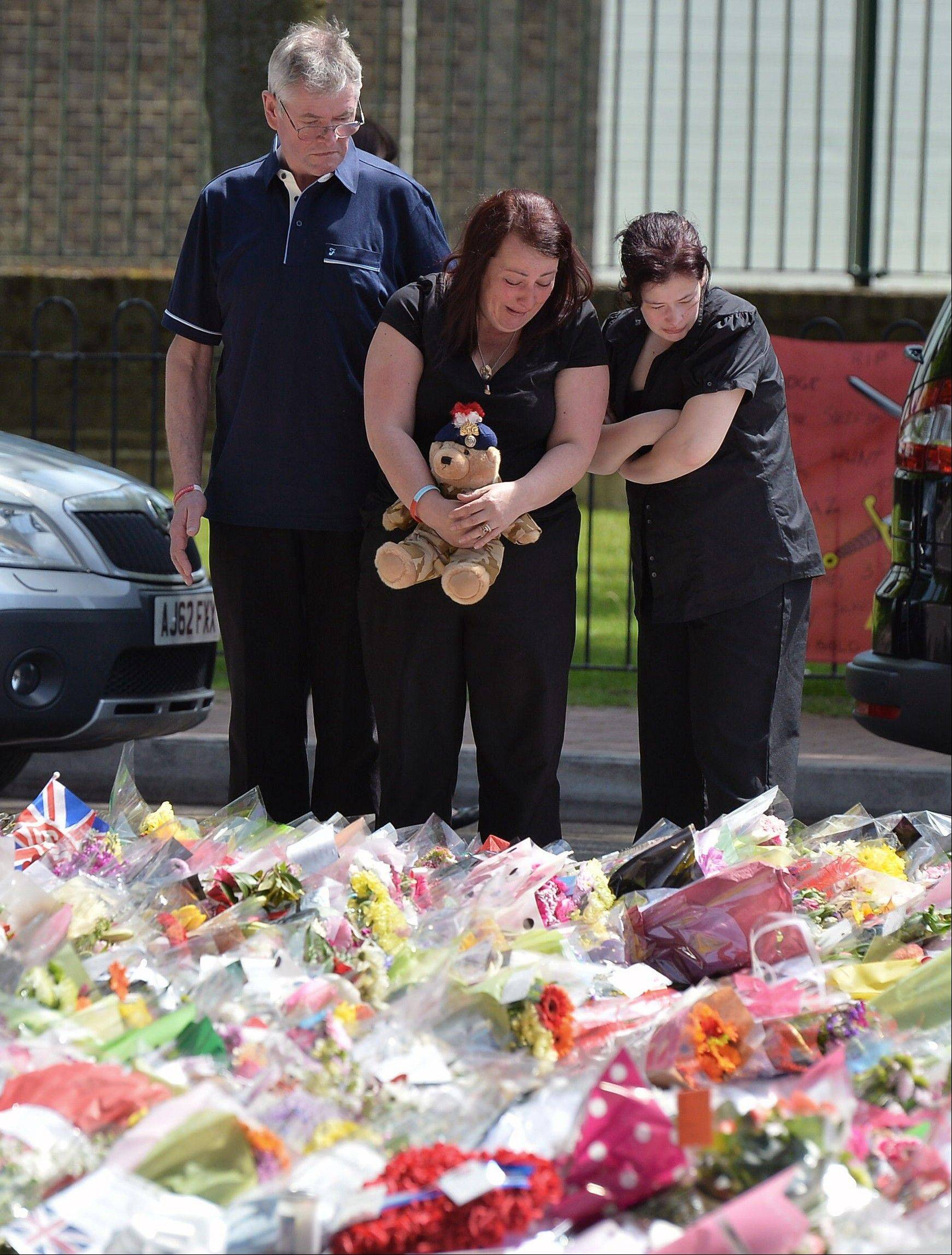 The mother of killed Drummer Lee Rigby, Lyn Rigby, centre, holds onto a teddy bear as she joins his stepfather Ian, and other family members looking at floral tributes outside Woolwich Barracks as they visited the scene of his murder in Woolwich, south-east London, Sunday May 26, 2013. Family members laid flowers at the Woolwich Barracks where the 25-year-old soldier of the Royal Regiment of Fusiliers Lee Rigby who was attacked and killed by two men in broad daylight Wednesday May 22, and where hundreds of floral tributes have been left by public well wishers.