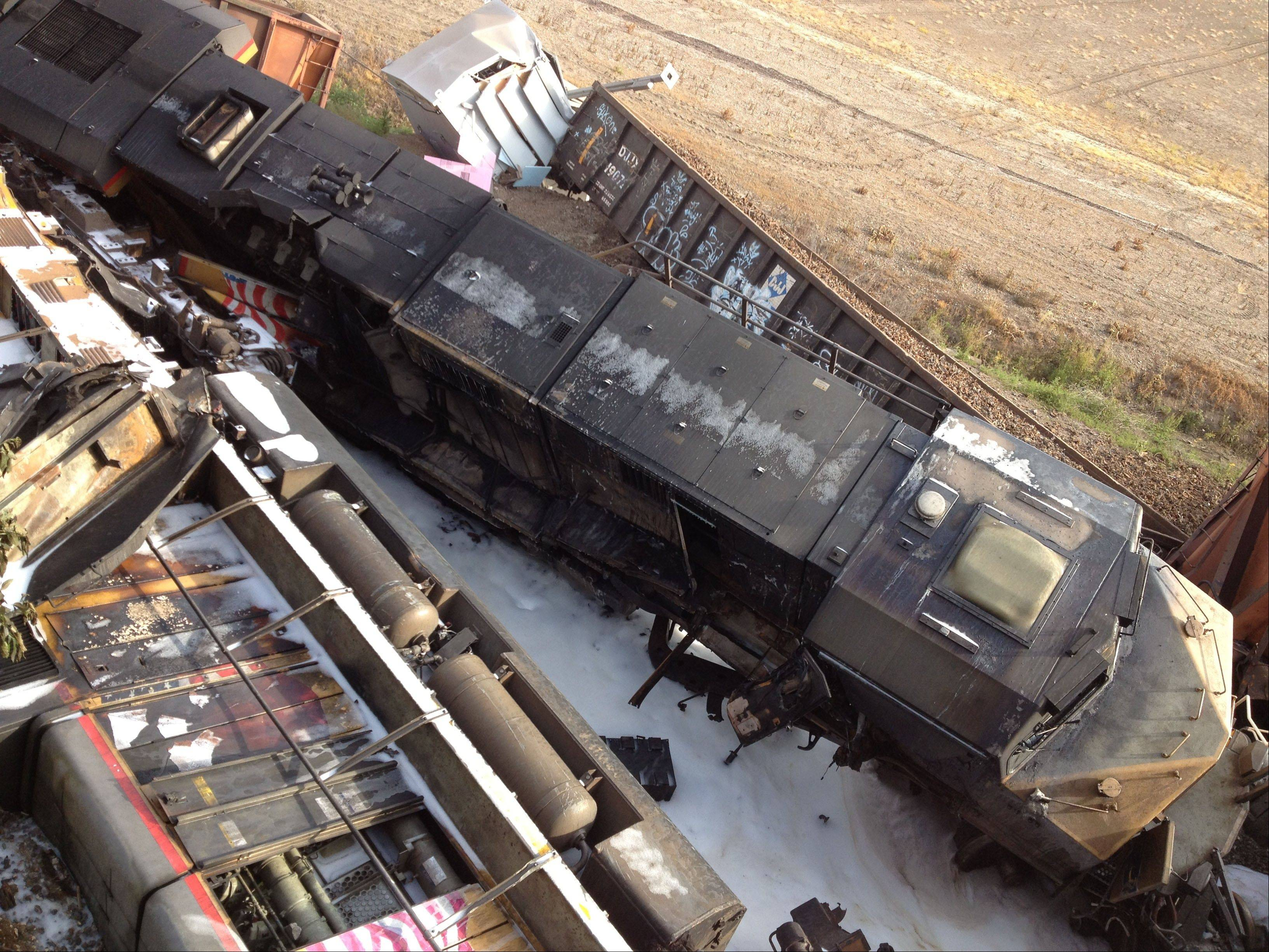 Damaged railcars lie on the ground near Rockview, Mo. on Saturday, May 25, 2013. Authorities said a highway overpass collapsed when rail cars slammed into one of the bridge's pillars after a cargo train collision. Seven people were injured, though none seriously.