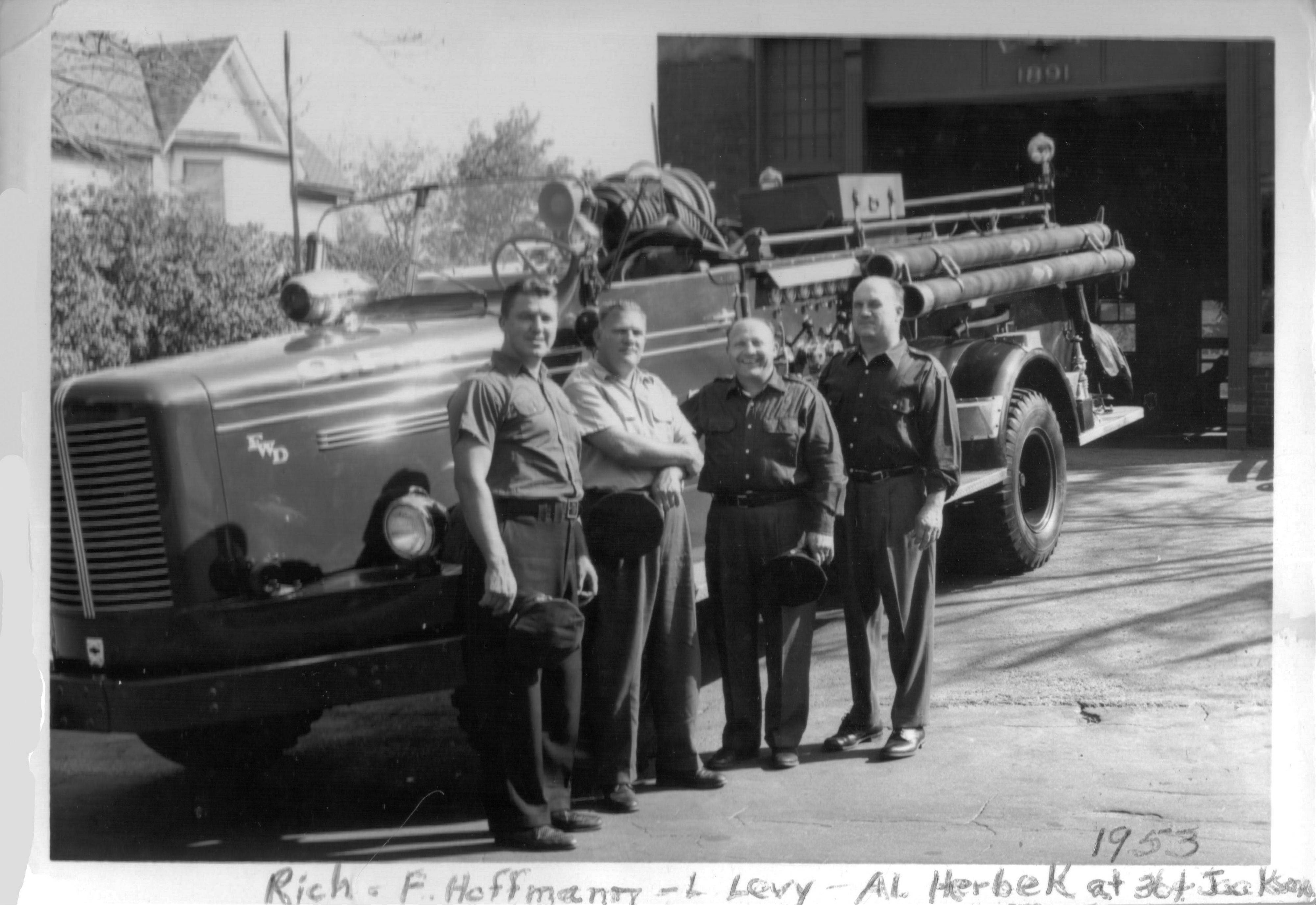 This 1953 photo provided by the Omaha Fire Department shows Richard Lang, left, standing with others next to a fire truck in Omaha, Neb.