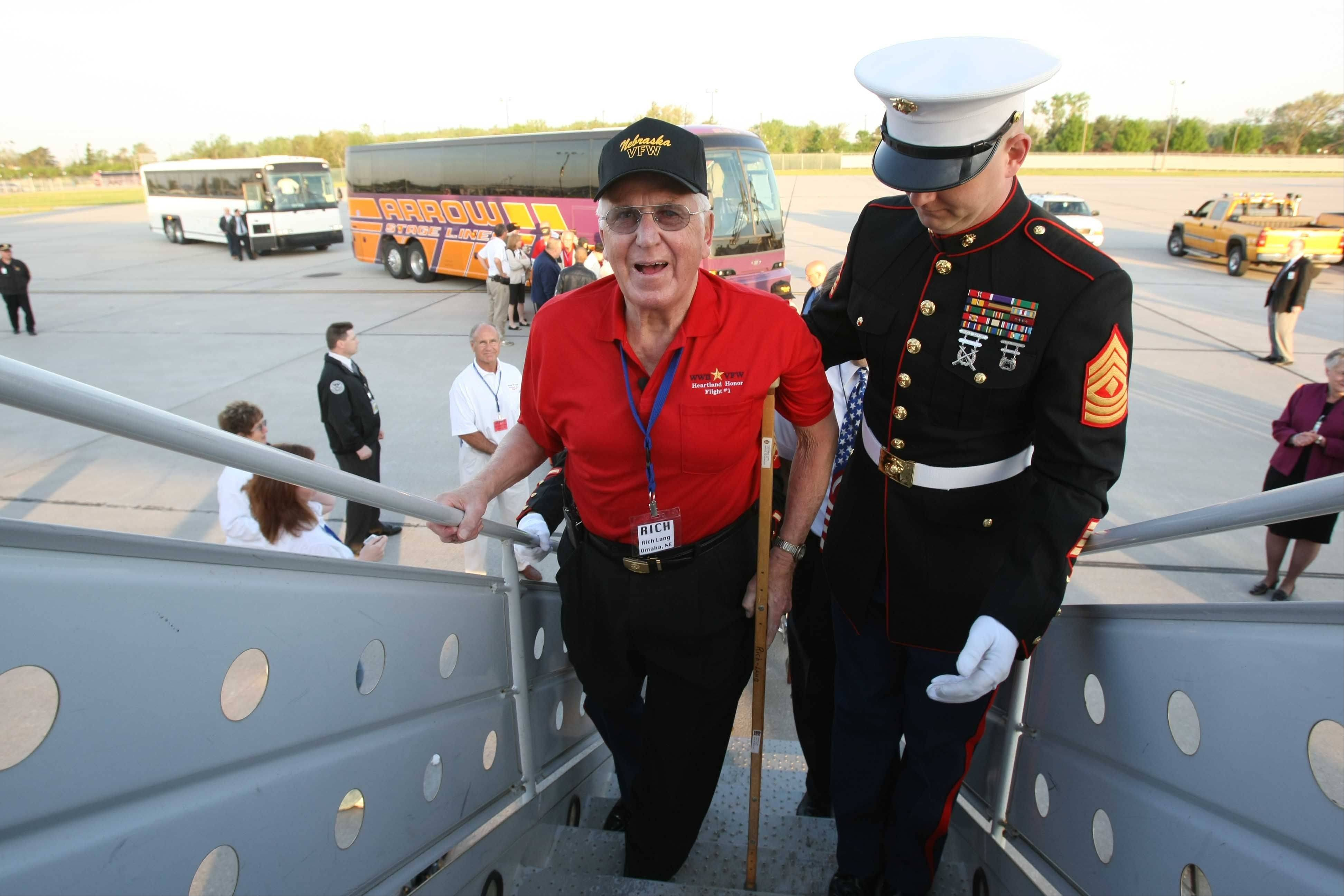 "In this May 21, 2008 photo, Richard Lang, whose right leg was amputated, is escorted up the flight stairs by Marine First Sgt. Wade Jensen at Eppley Airfield in Omaha, Neb. during an Honor Flight to Washington for World War II veterans. Bill Williams, whose company sponsored the event, advised him there was a steep set of plane stairs. ""I made my big mistake,"" Williams recalls. ""I said, 'We will carry you.' ... He said, 'Listen pal, I haven't been carried since Guam.'"""