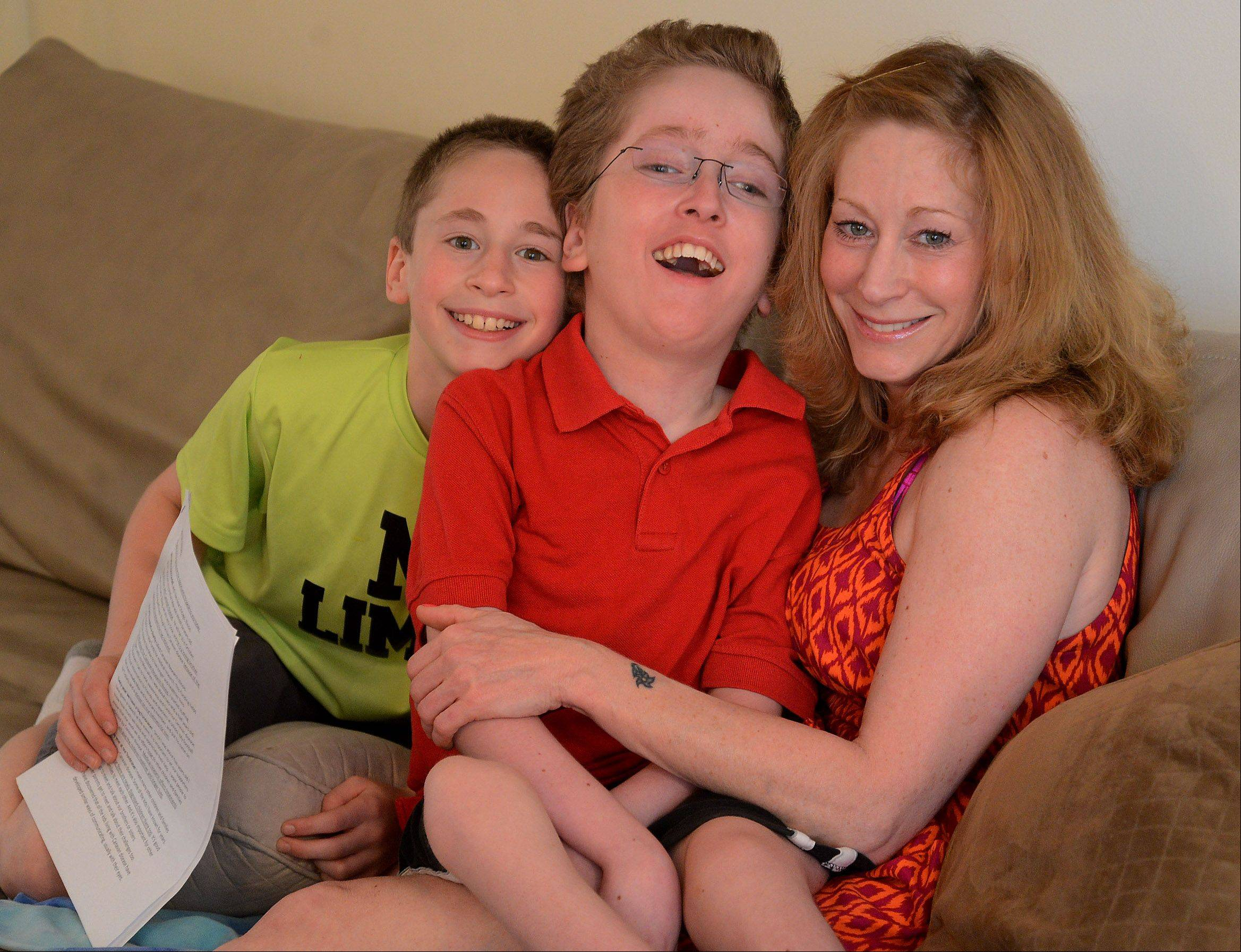 His disability prevents him from talking, but Max Randell, center, smiles broadly whenever he cuddles with his mom, Ilyce, and younger brother, Alex.