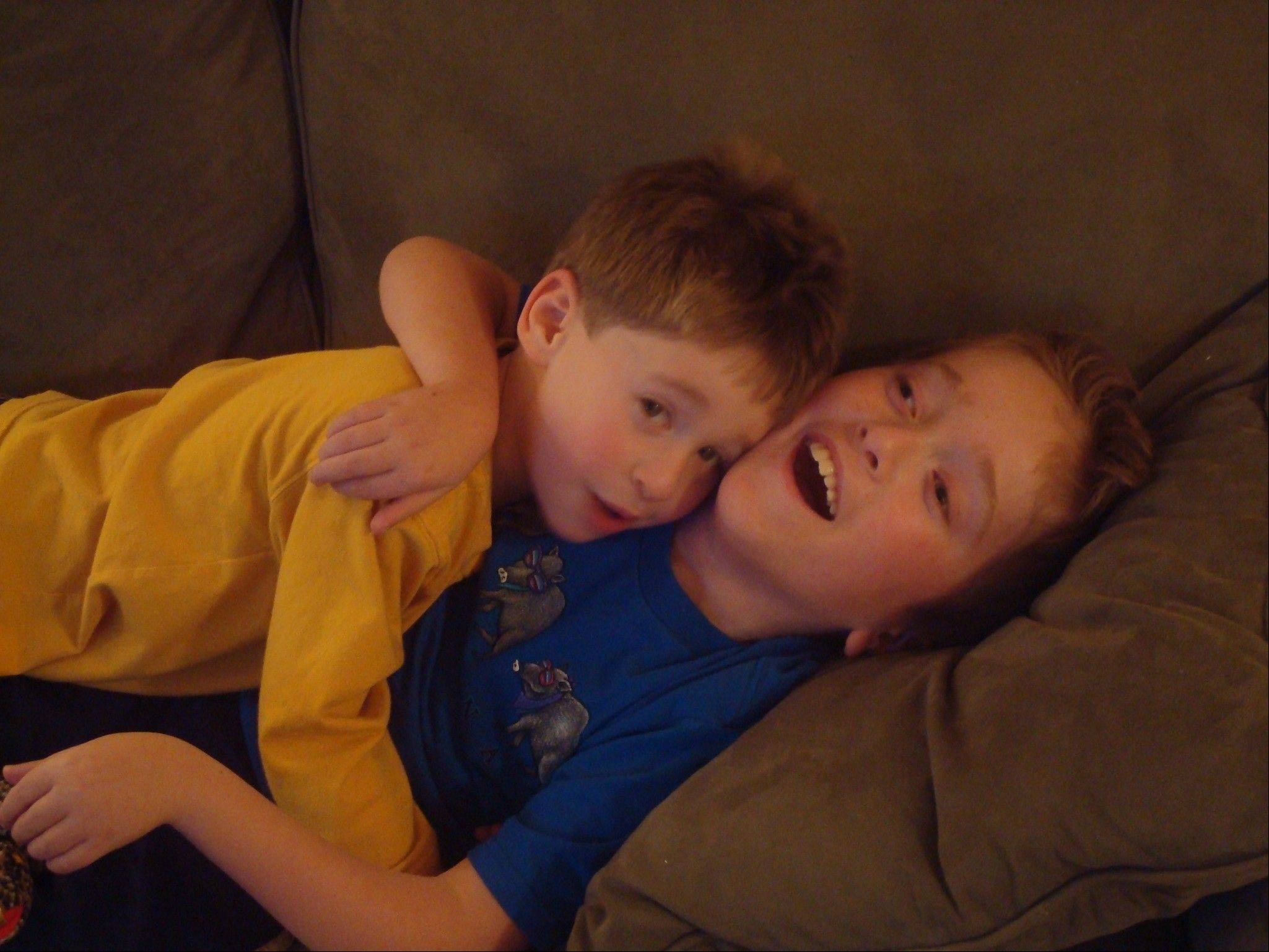 As younger boys, Alex, left, and Max Randell would lie together on the couch. Now a 10-year-old wrestler, Alex, remains gentle with his 15-year-old brother who has a rare disease that robs him of most movement and the ability to speak.