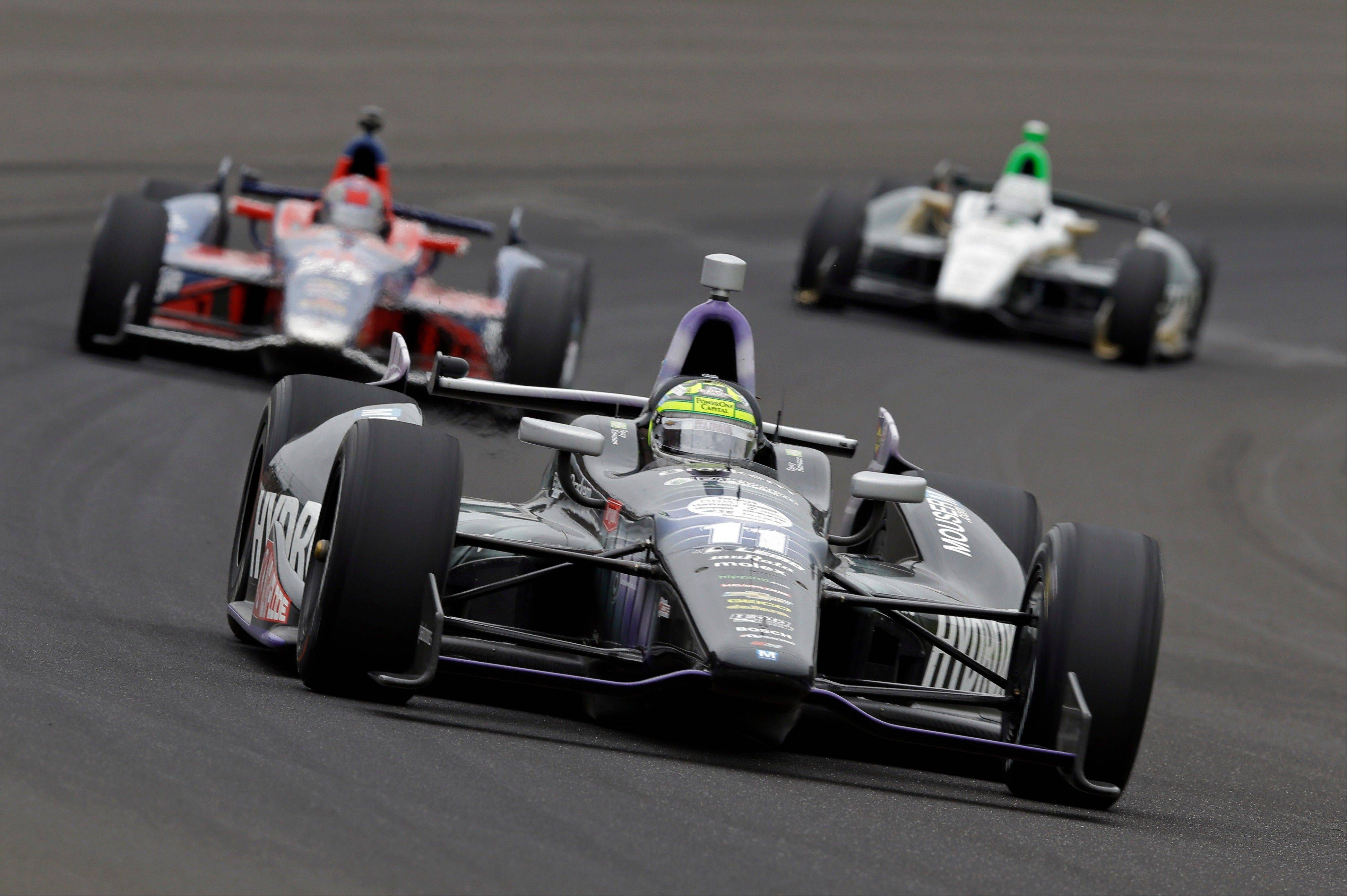 Tony Kanaan, of Brazil, drives through the first turn during the Indianapolis 500 auto race at the Indianapolis Motor Speedway in Indianapolis Sunday, May 26, 2013.