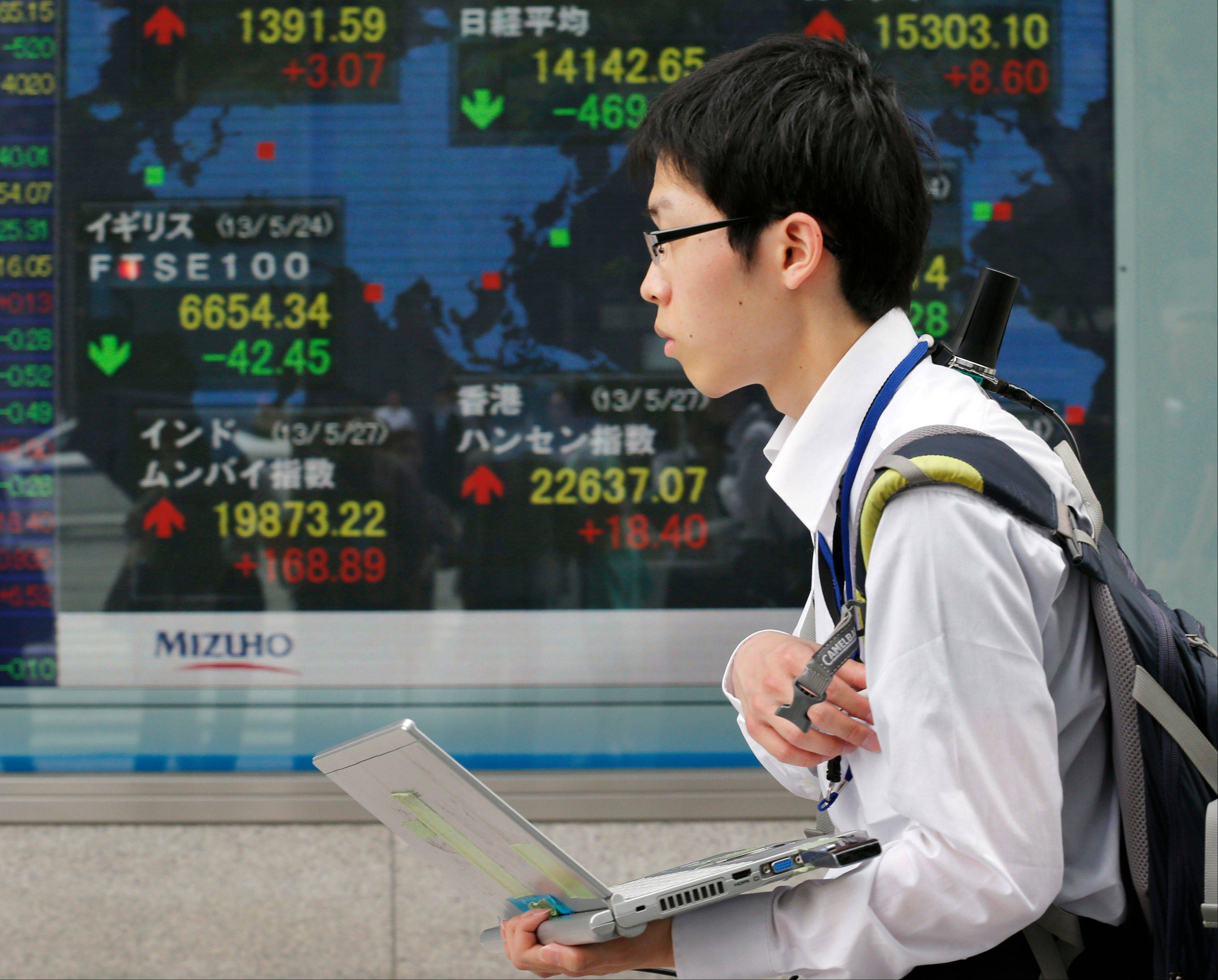 A youth walks by an electronic stock board of a securities firm in Tokyo Monday, May 27, 2013. The Nikkei 225 closed down 469.80 points, or 3.22 percent at 14,142.65 Monday after the yen reversed some of its recent fall against the U.S. dollar. Stocks elsewhere in Asia were mixed as investors tried to sort out conflicting indicators about the health of the global economy.
