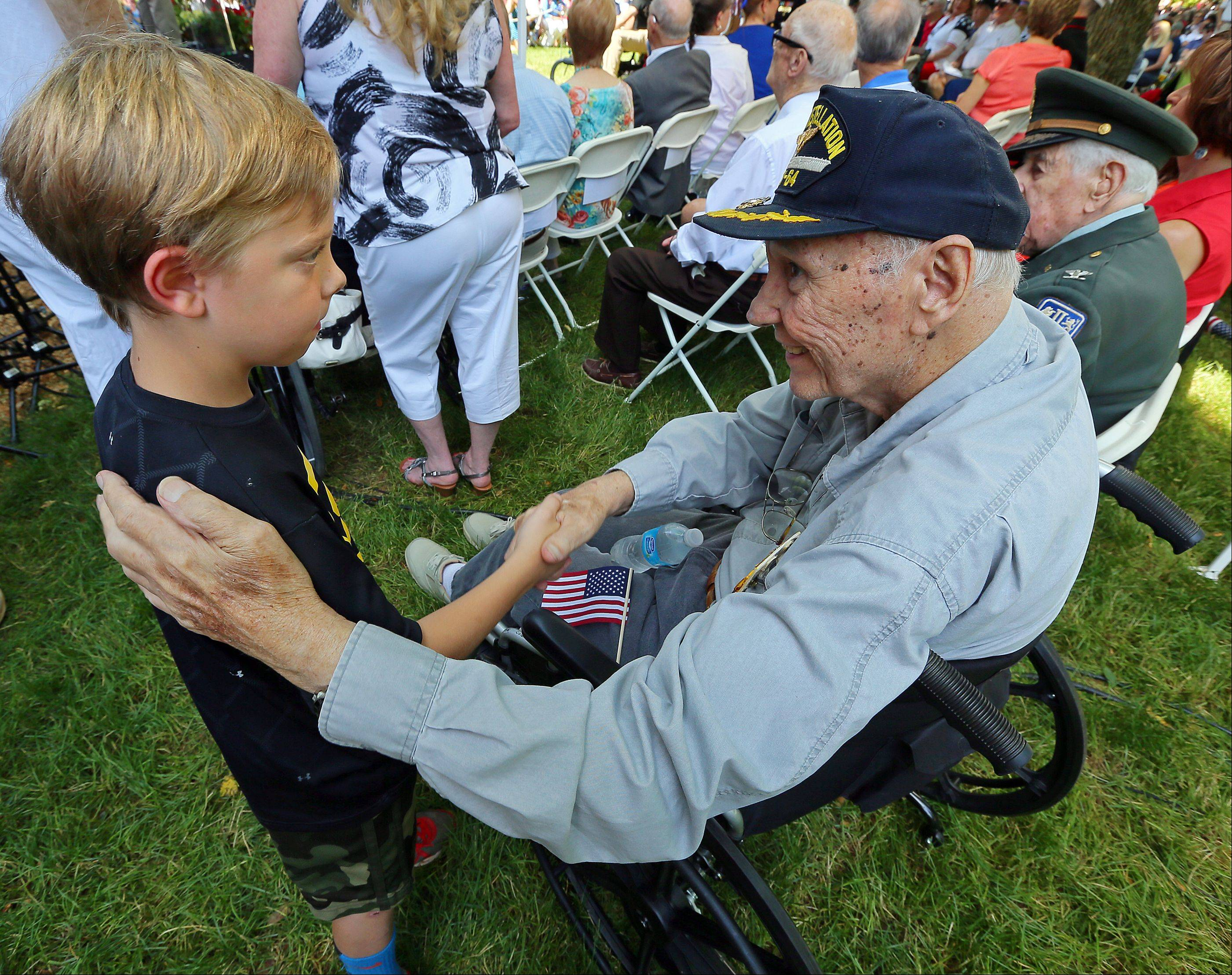 Eight-year-old Jackson Turman shakes the hand of World War II Navy Veteran and Vietnam Veteran Frank Coleman, 85, of Roswell, after giving him a salute during the �Roswell Remembers� Memorial Day military ceremony at city hall on Monday, May 27, 2013, in Roswell, Ga. Coleman returned the salute and gave the young man a hug. Turman was attending the Memorial Day service with his grandfather Russ Johnson of Roswell, who is a Marine Vietnam veteran.