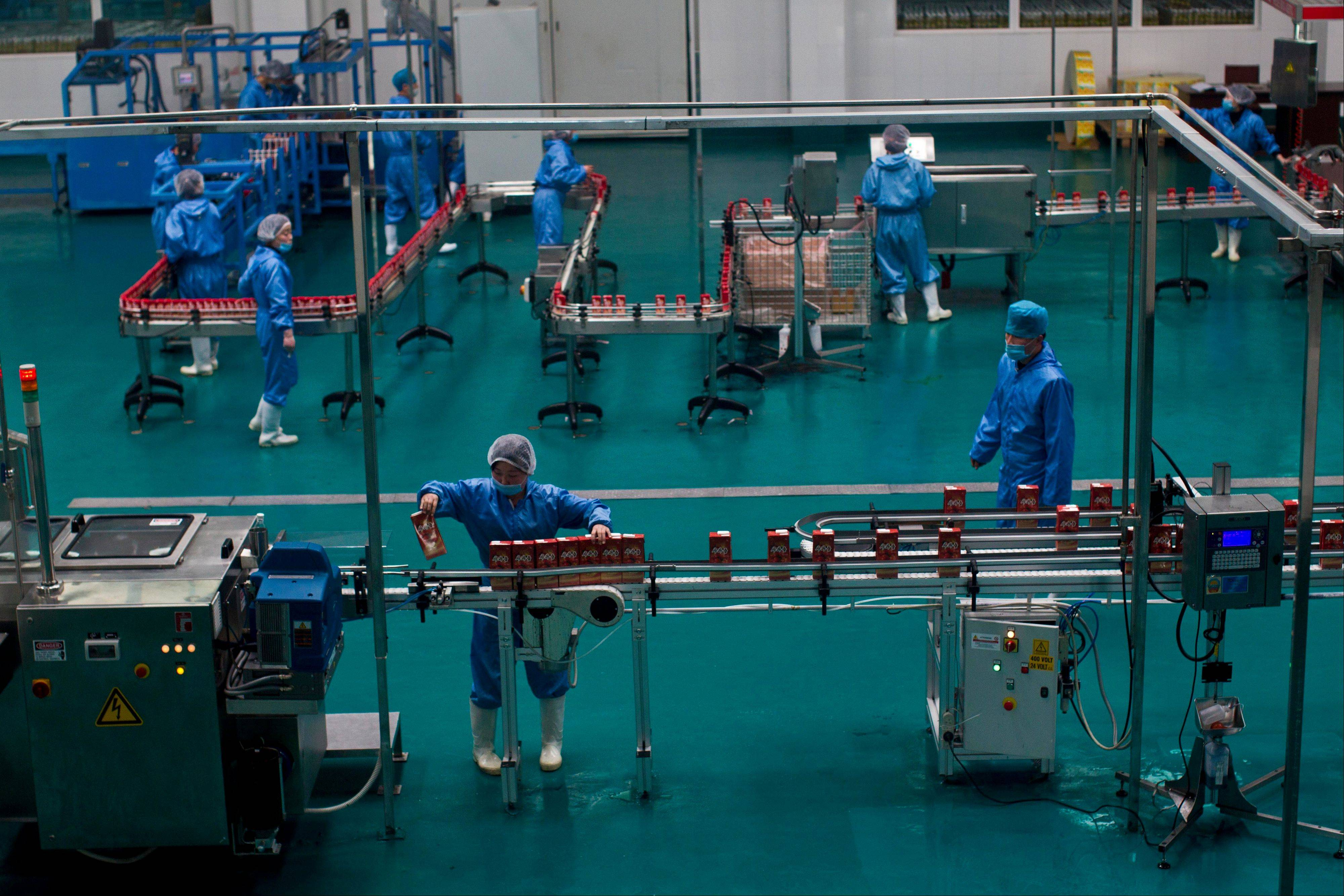 In this Tuesday, April 10, 2012 photo, North Koreans work at a factory bottling apple juice on the grounds of a communal apple farm on the outskirts of Pyongyang, North Korea. A North Korean economist said that the government introduced new economic management methods in April 2013 that relax state control of workers' salaries.