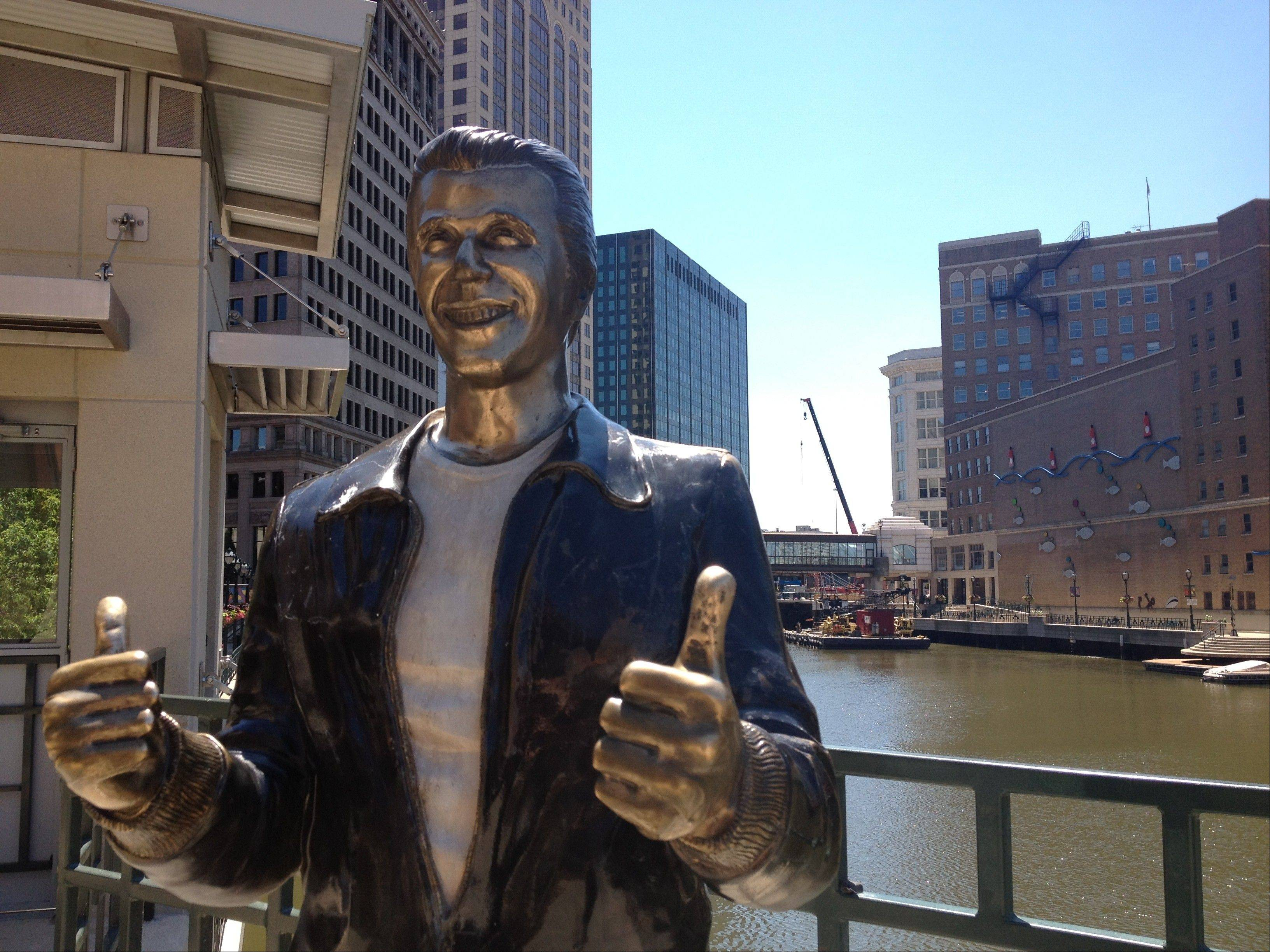 "This June 26, 2012 photo shows ""The Bronze Fonz,"" a statue in the image of the character The Fonz, played by Henry Winkler in the 1970s series ""Happy Days,"" along the Milwaukee Riverwalk. The statue evokes wistful memories of prosperity when more than half of the adult workforce had factory jobs with manufacturers like Allis-Chalmers, that are defunct."