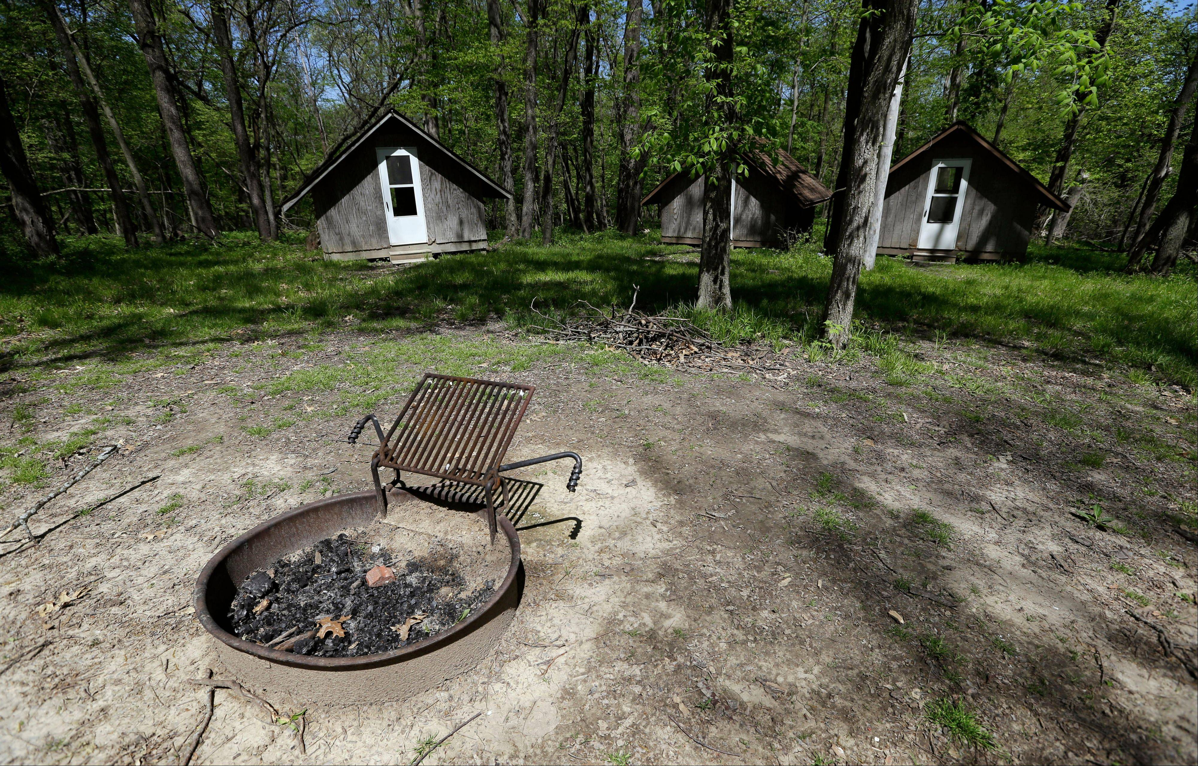 This Tuesday, May 14, 2013 photo shows a fire pit and cabins at the Camp Conestoga Girls Scouts camp, in New Liberty, Iowa. In an effort to save money, Girl Scout councils across the country are making proposals that would have been unthinkable a generation ago: selling summer camps that date back to the 1950s.